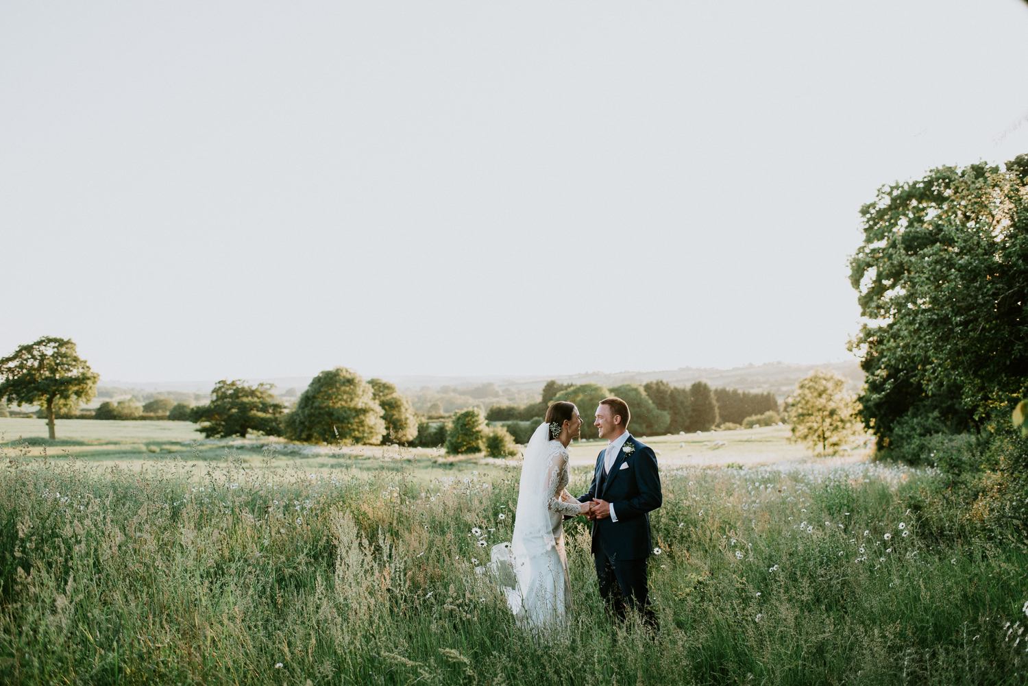 Bride and Groom portrait of a giggle in the middle of a sunset lit countryside field. These two had an intimate wedding celebration in rural Warwickshire.