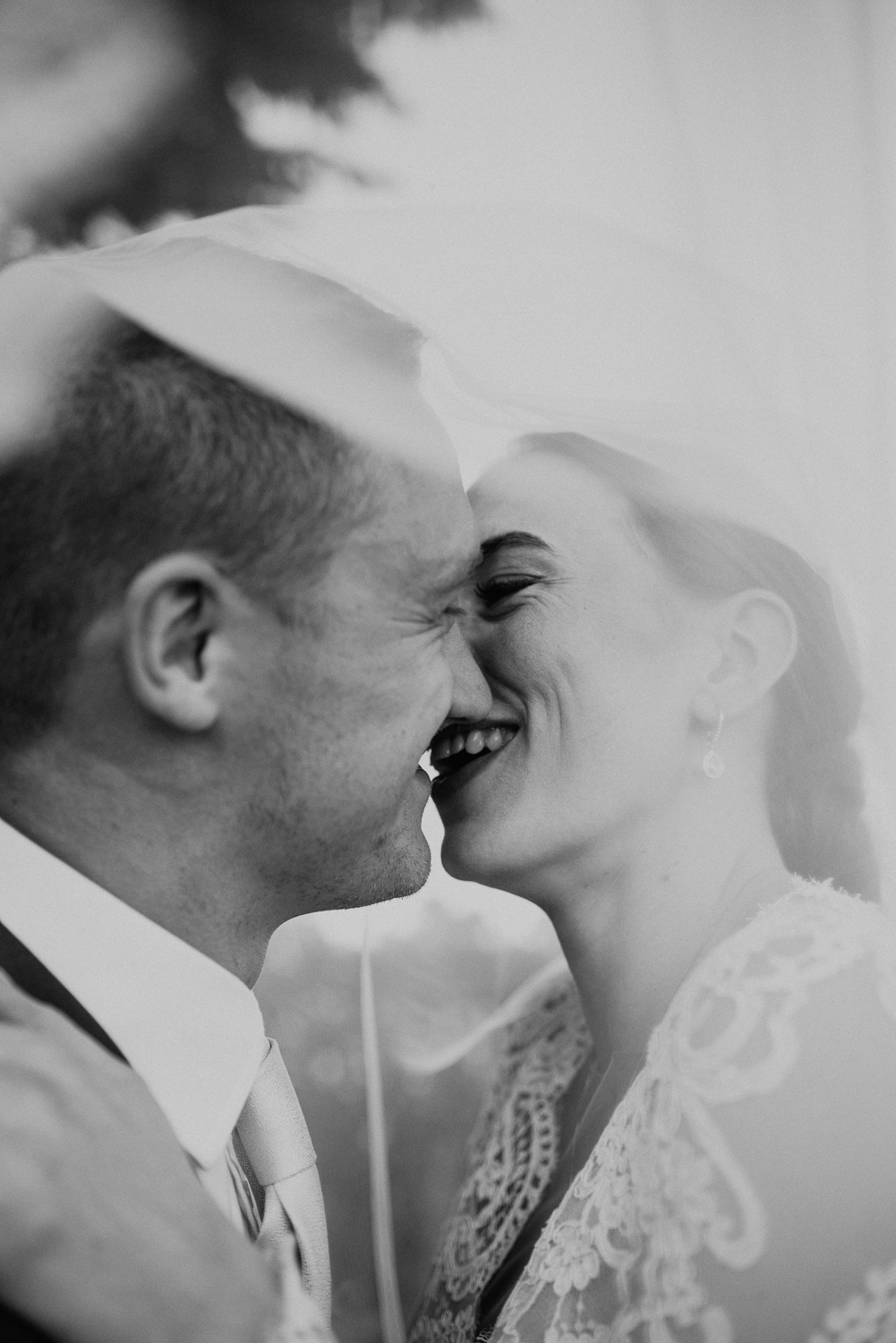 Bride and Groom portrait of a giggly kiss under the veil. These two had an intimate wedding celebration in rural Warwickshire.