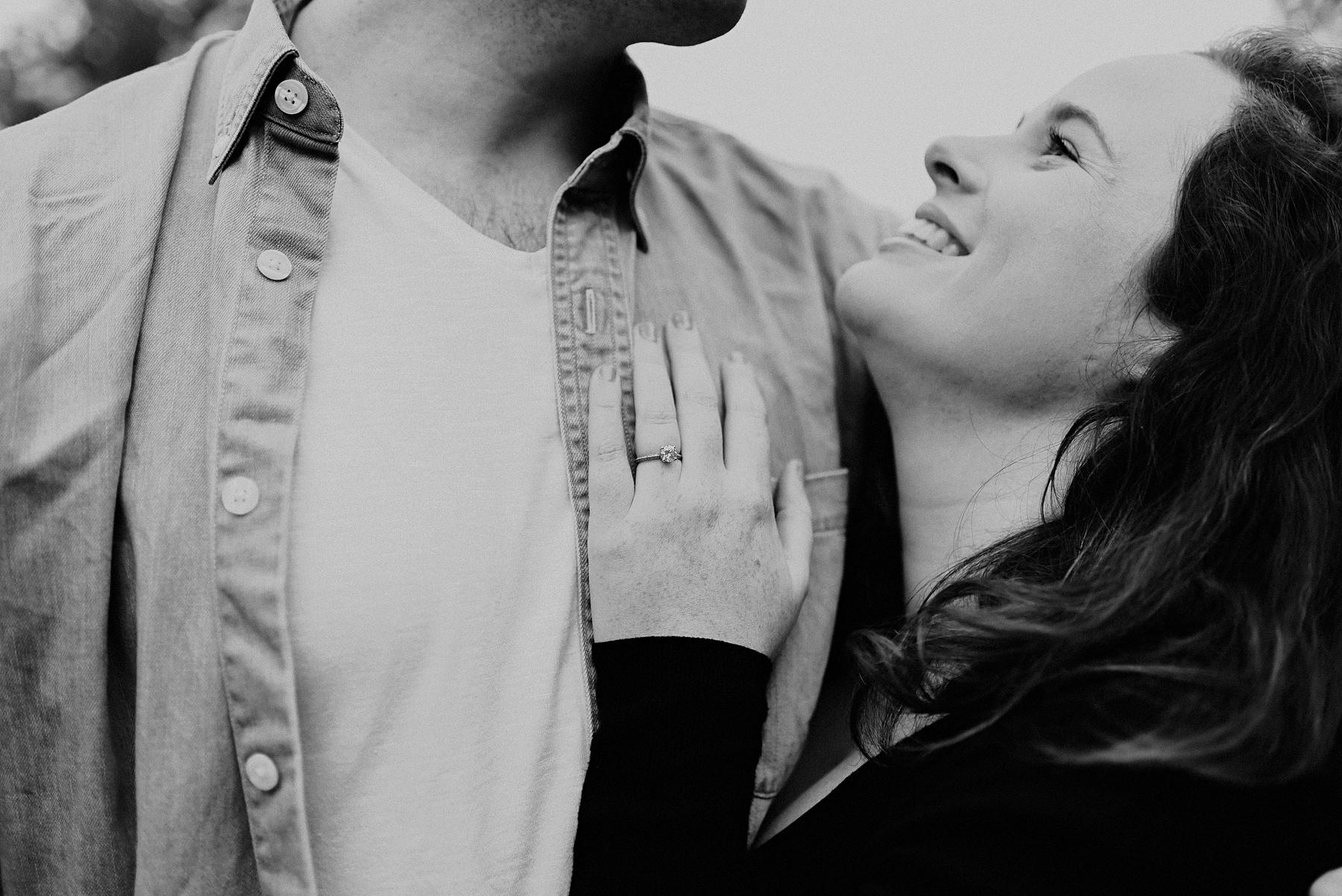 A black and white intimate portrait of a couple in Richmond park. She is looking up at him, smiling, and showing off her engagement ring on his chest.