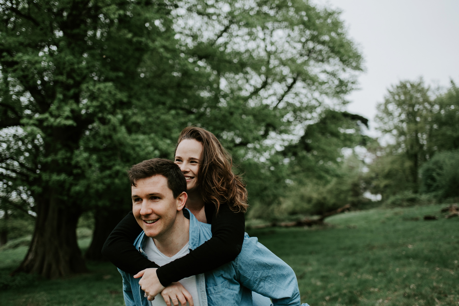 A playful portrait of a couple in Richmond park. He is giving her a piggy back ride and they are both smiling. It is spring and they are having an engagement session.