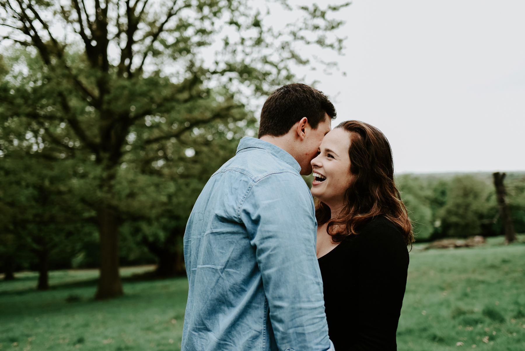 A playful portrait of a couple in Richmond park. He is whispering something into her ear and she is laughing.