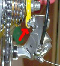 """The red arrow points to a """"B"""" adjusting screw that rests on the   frame's dropout. Newer rear derailleurs have the """"B"""" adjusting   screw located on the pulley wheel cage where it joins the rear derailleur body."""