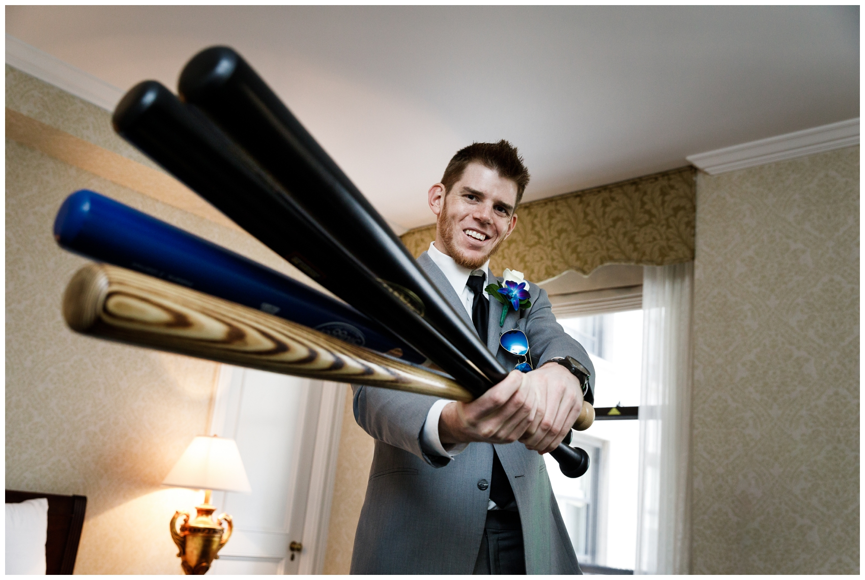 groom holding baseball bats