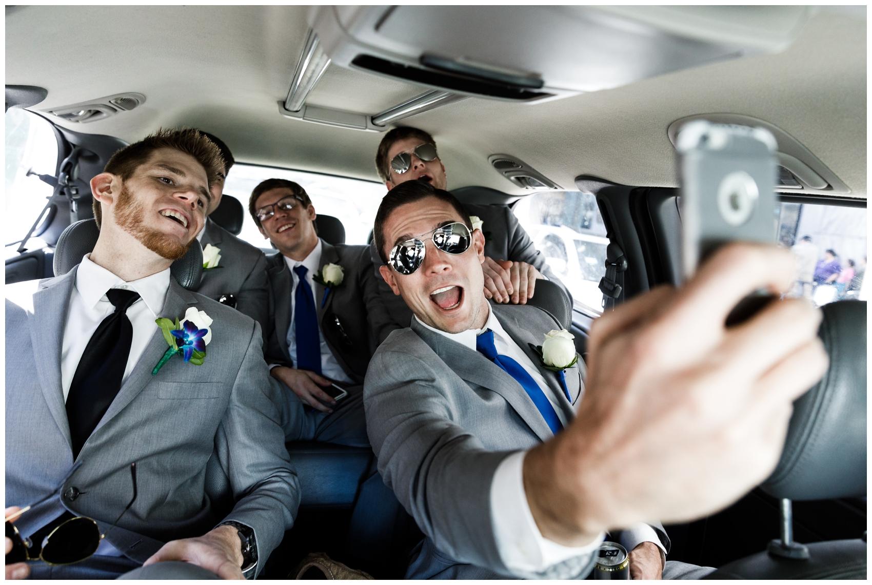 groomsmen and groom taking a selfie in a car
