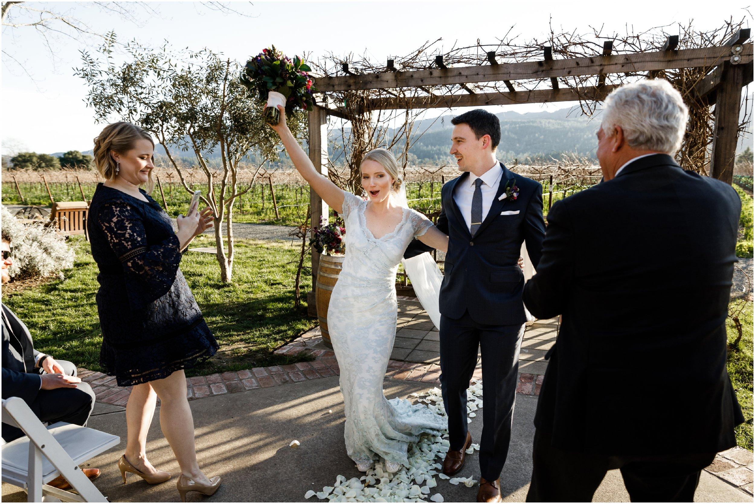 bride raising bouquet during wedding recessional
