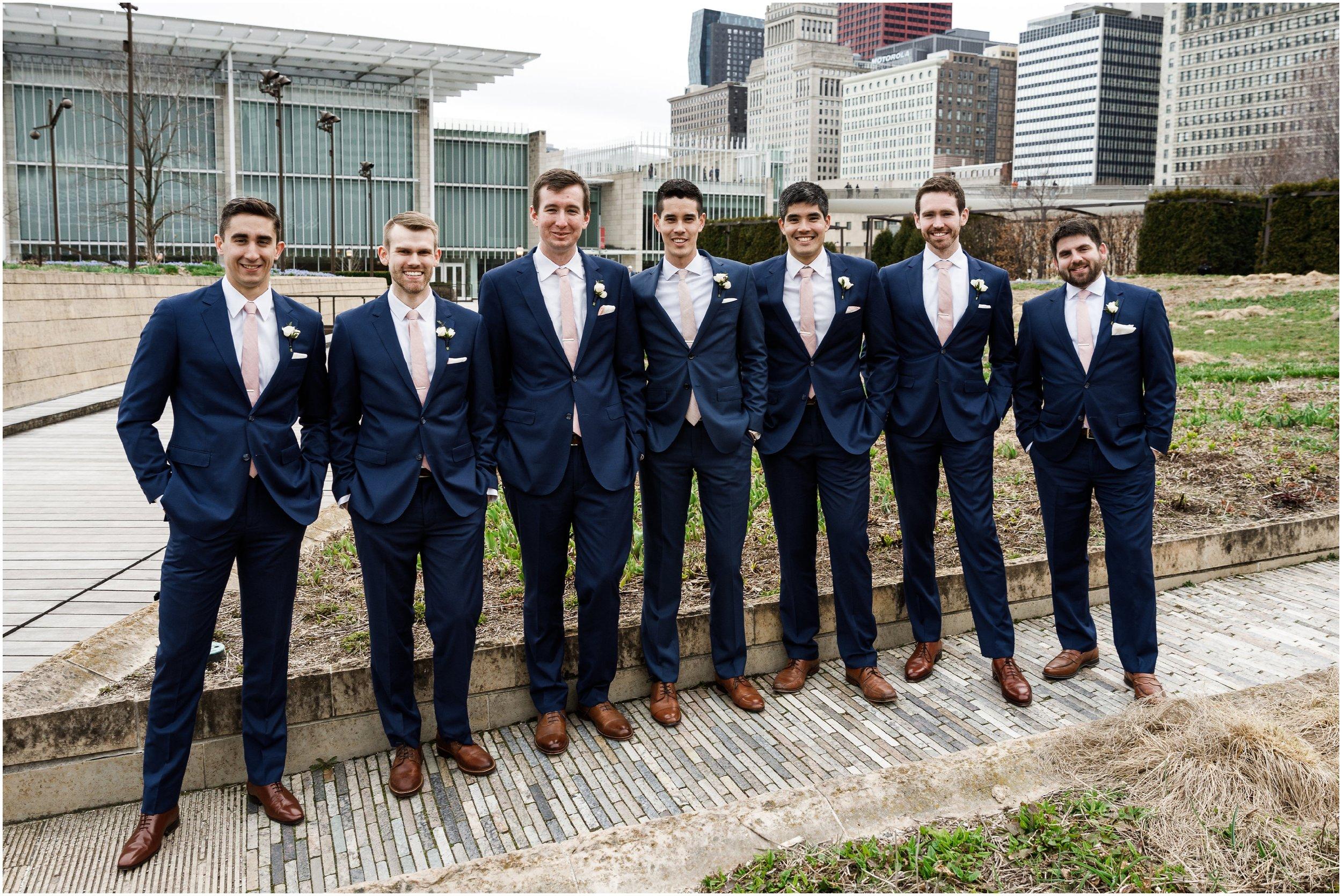 groom and groomsmen  posing in Millennium park's Lurie garden