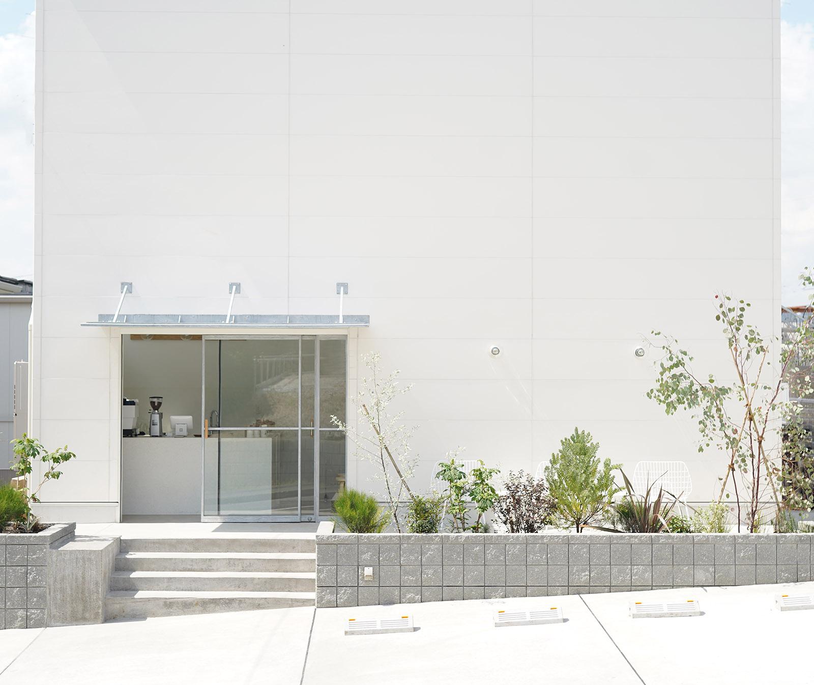 建物を正面に見て、右側の壁面に白色のスタジオ玄関ドアがあります