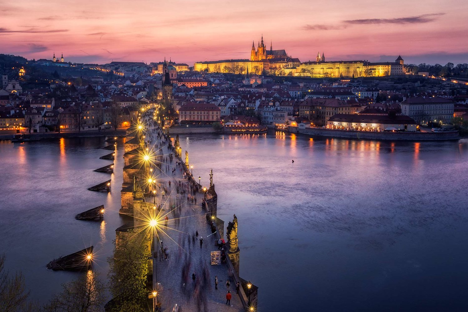 Charles bridge at dusk in front of Prague Castle on the horizon in Prague, Czech Republic