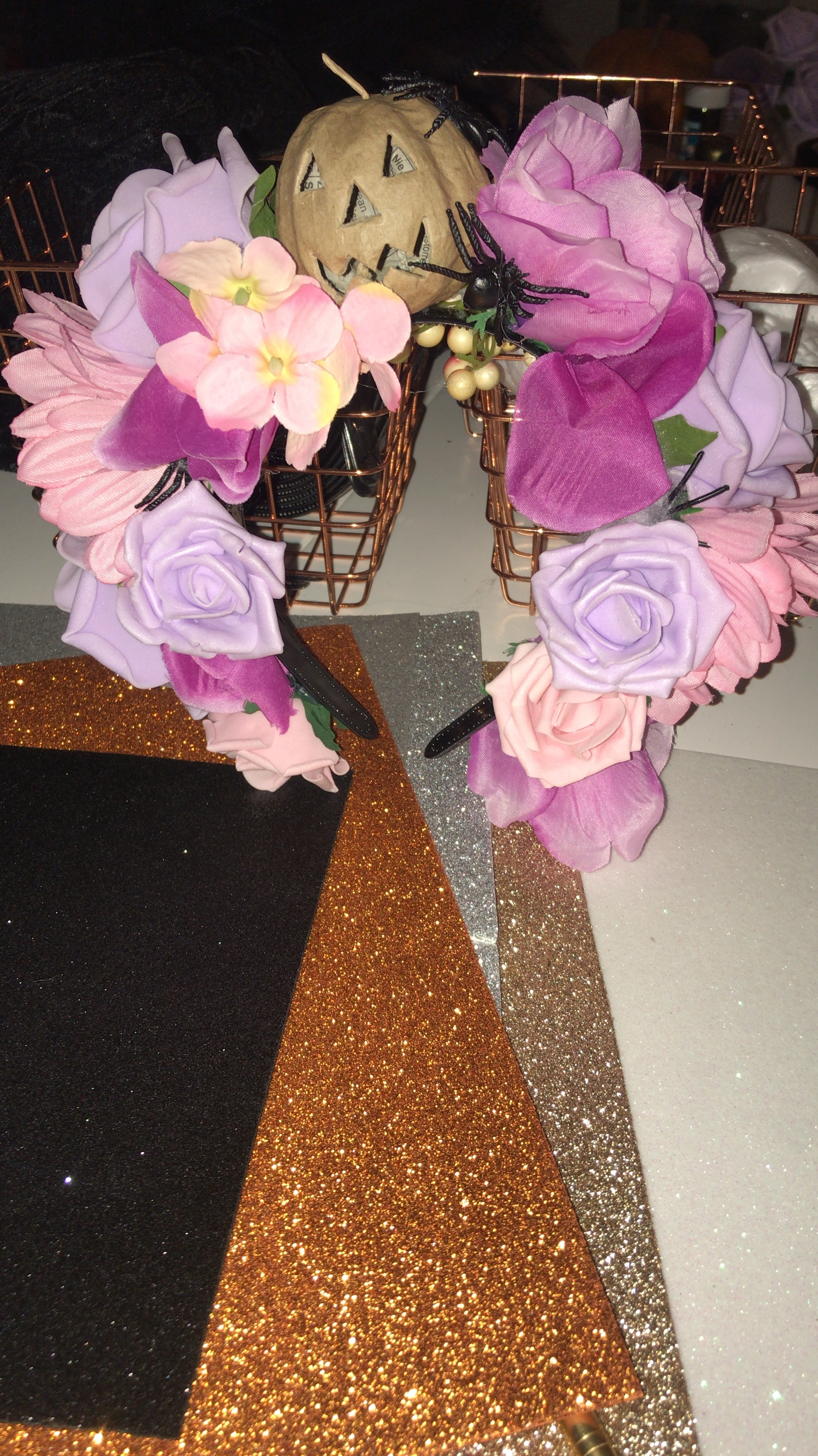 I attached the flowers to the headband using the glue gun and then added in a pumpkin decoration and a couple creepy crawlies to make it more…Halloween-y.