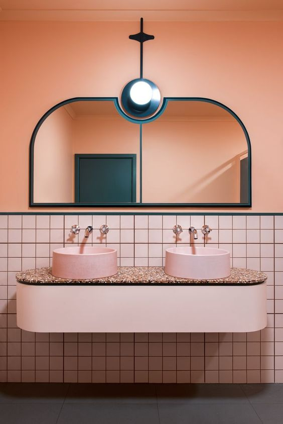 The peach colour featured on the walls of this gorgeous bathroom designed by  Bergman & Co  is beautifully offset against those pink basins and terrazzo unit.