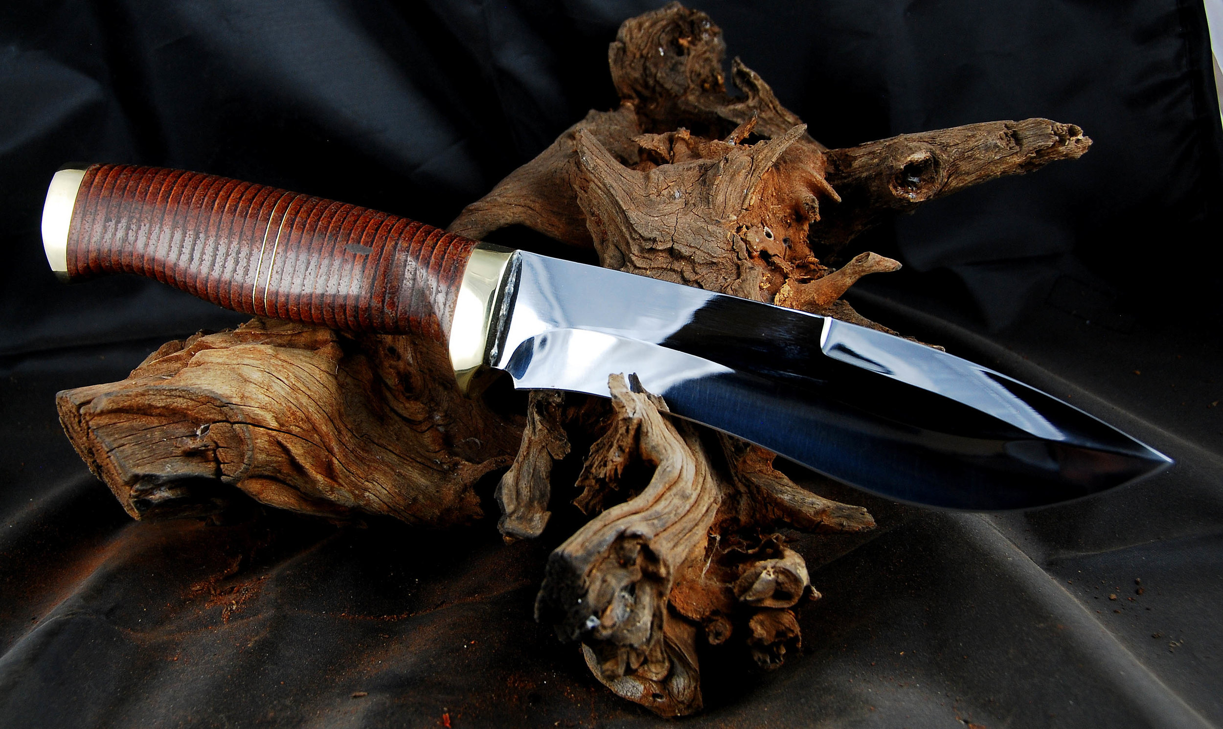 Broad bladed hunter with a stacked leather handle