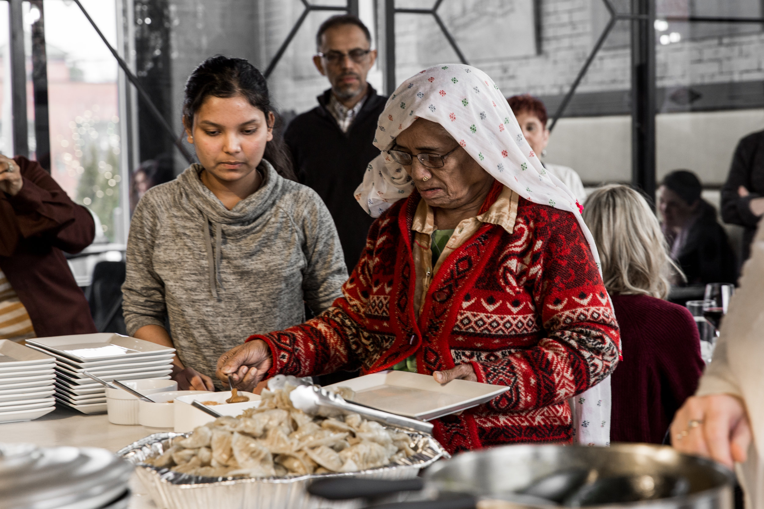 Cooking class instructor Hema (left) and her aunt sample food from the Nepali cooking class they taught.