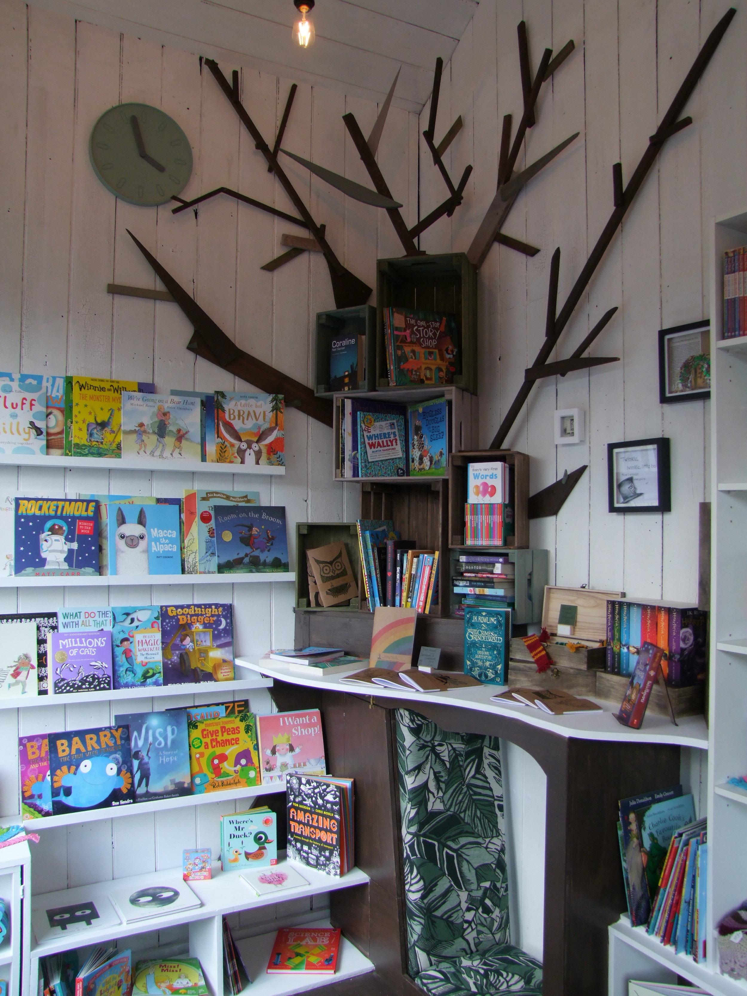 Through the Wardrobe Children's Bookshop Interior tree sculpture and reading nook