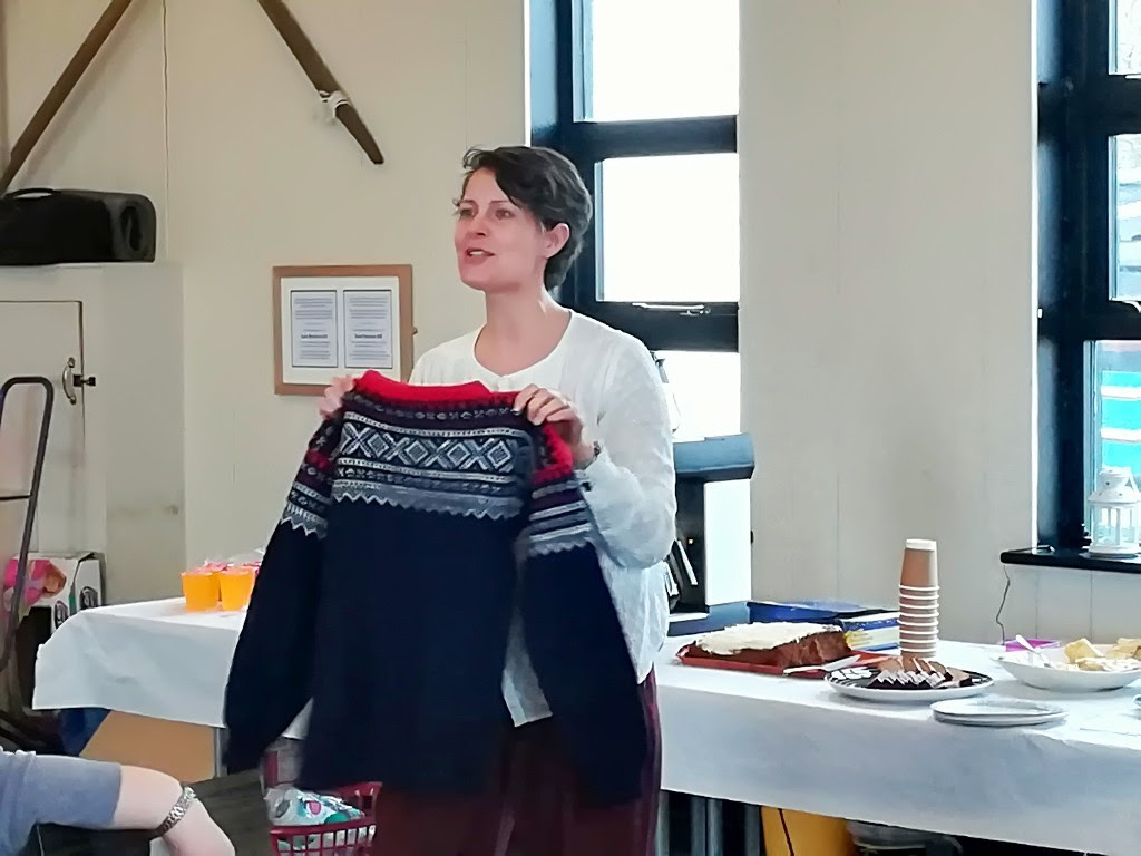 Dr Torun Kjolberg speaking about Norwegian history and tradition of Knitting, showing a Marius patterend jumper
