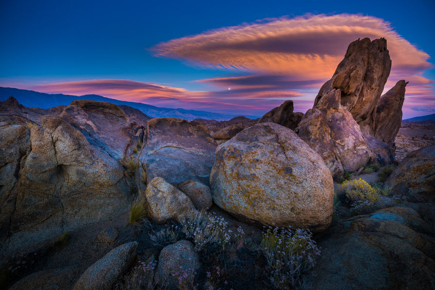 Lenticular clouds form over the rock formations of the Alabama Hills