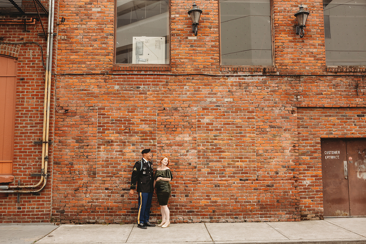 Newlywed couple with brick wall backdrop