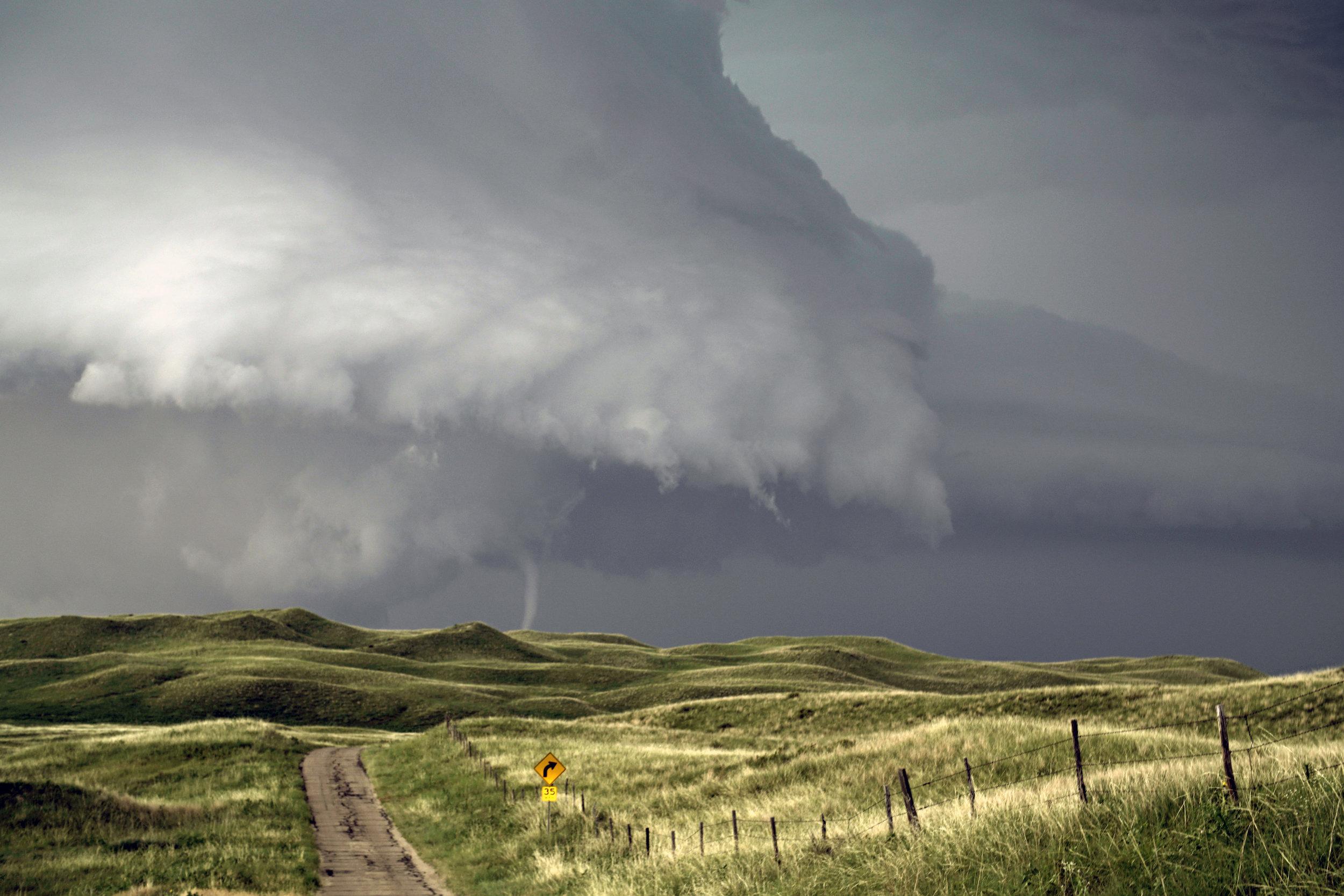 A massive supercell thunderstorm spawns a tornado in the sand hills region of Nebraska.