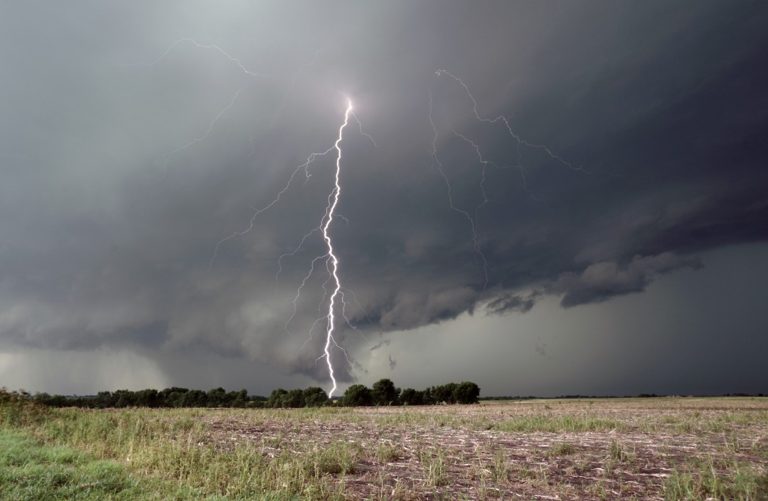 A tall cloud-to-ground lightning strike precedes the development of a tornado, northwest Missouri.