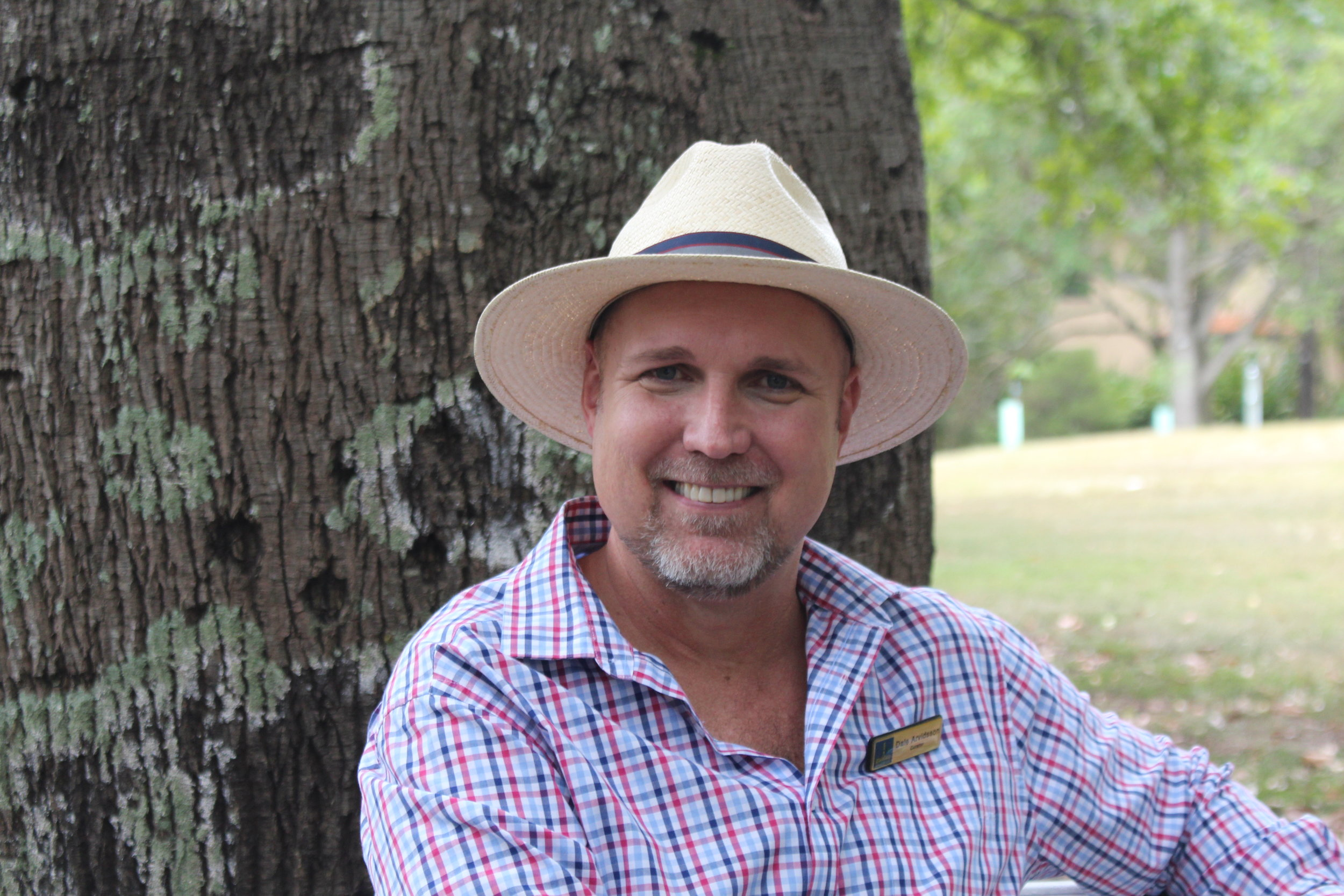 Dale Arvidsson, curator of Brisbane's Botanic Gardens, sitting in front of  Brachychiton rupestris , the Queensland bottle tree.