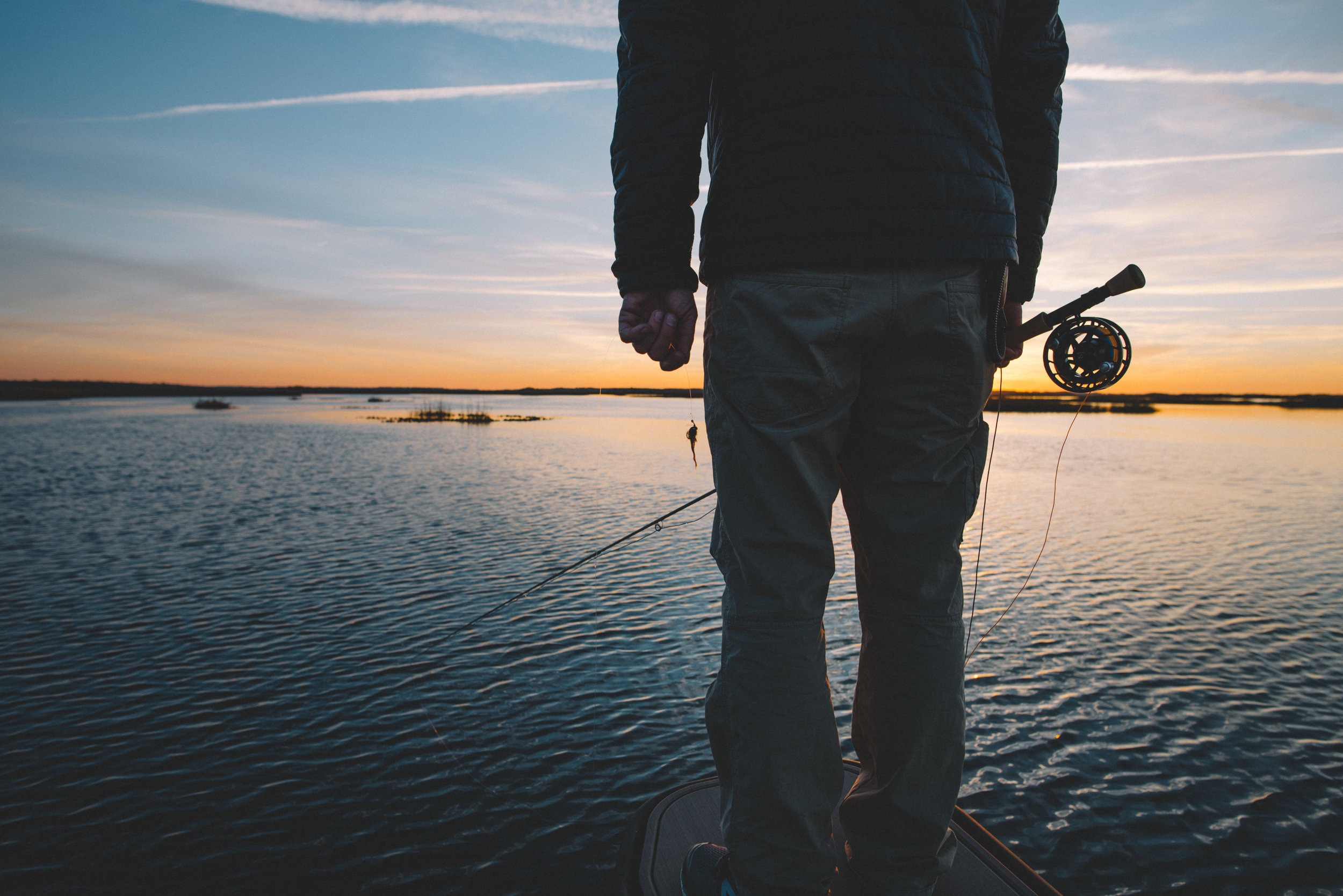 Copy of Angler standing with fly rod in hand at sunrise