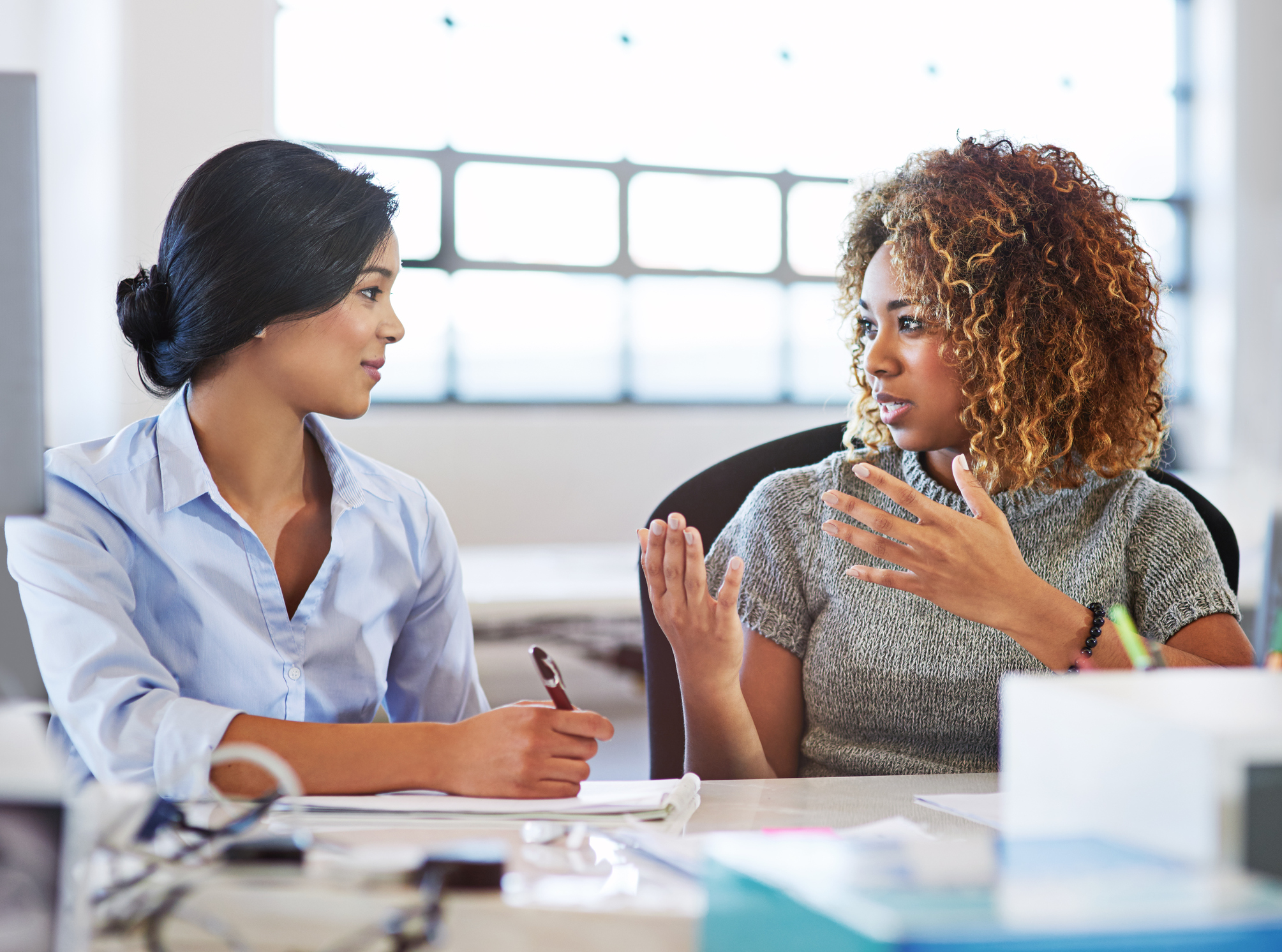 Photo Credit:  gradyreese/iStock / Getty Images . Two people at a table look at each other. One of them holds a pen, the other is gesturing while speaking.