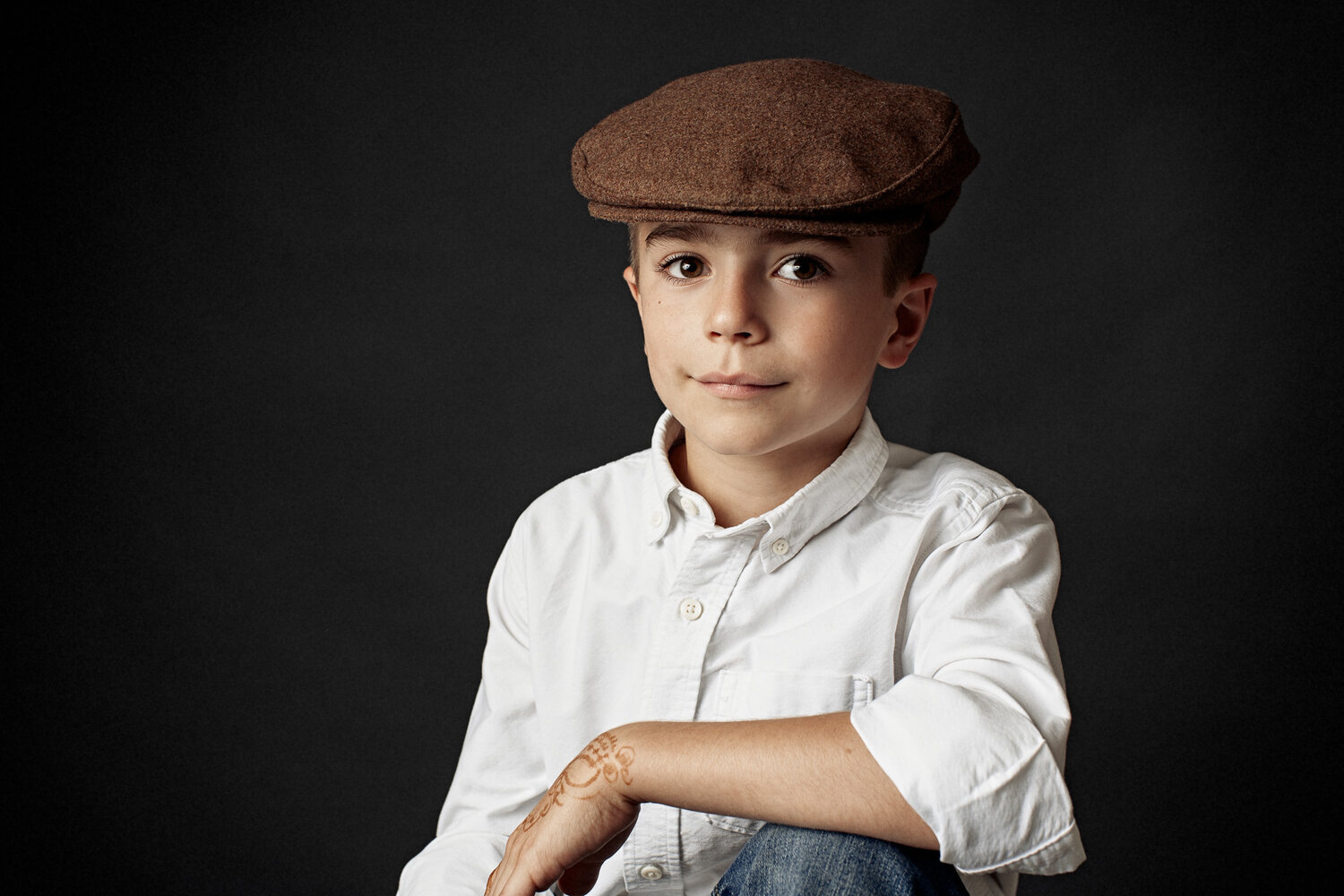 portrait of boy sitting with golf cap and white shirt new braunfels photography studio