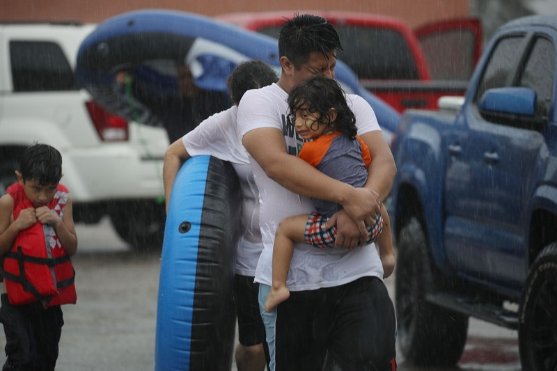 Mario Qua holds Wilson Qua as they evacuate their flooded home after the area was inundated with flooding from Hurricane Harvey on August 27, 2017 in Houston, Texas. (Photo by Joe Raedle/Getty Images)  From the Palm Beach Post.