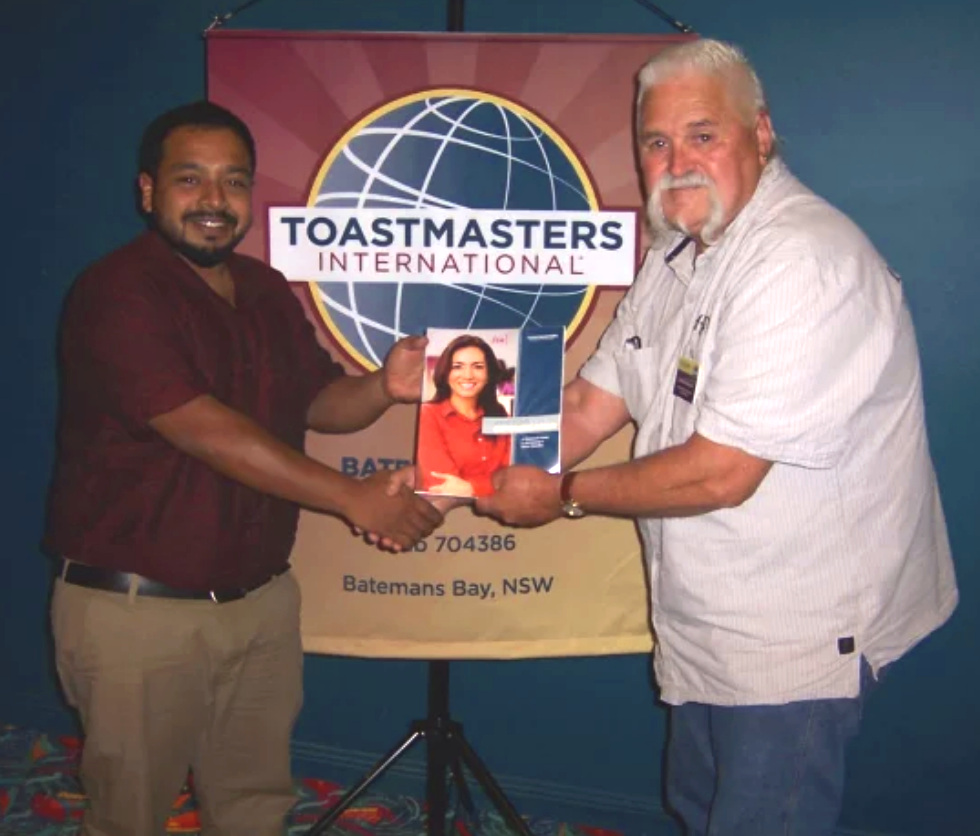 Moosa is presented with his first Toastmasters manual by President Noal Annabel