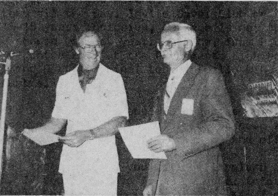 Peter Bell receives the winner's certificate from Area Governor Leon Taylor who was chief judge of the contest.
