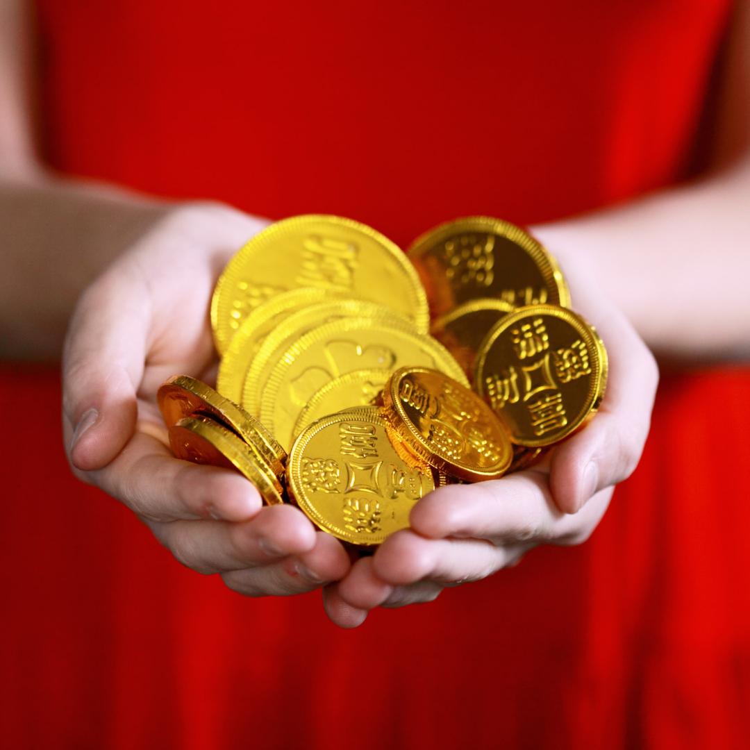 Image Description: A photo of light-skinned hands holding large, golden feng shui coins.