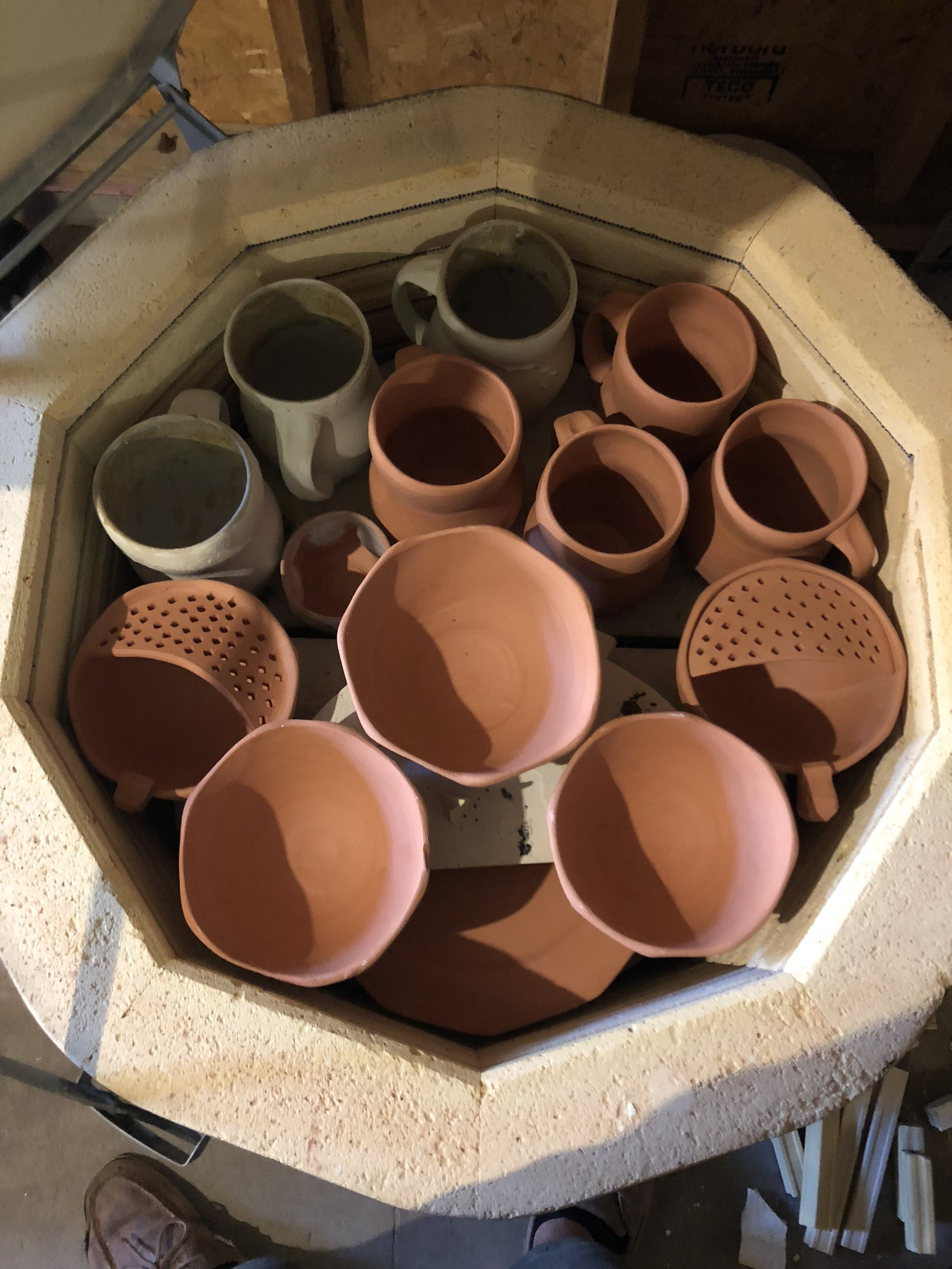 A kiln load of recently bisqued pots before it is unloaded.