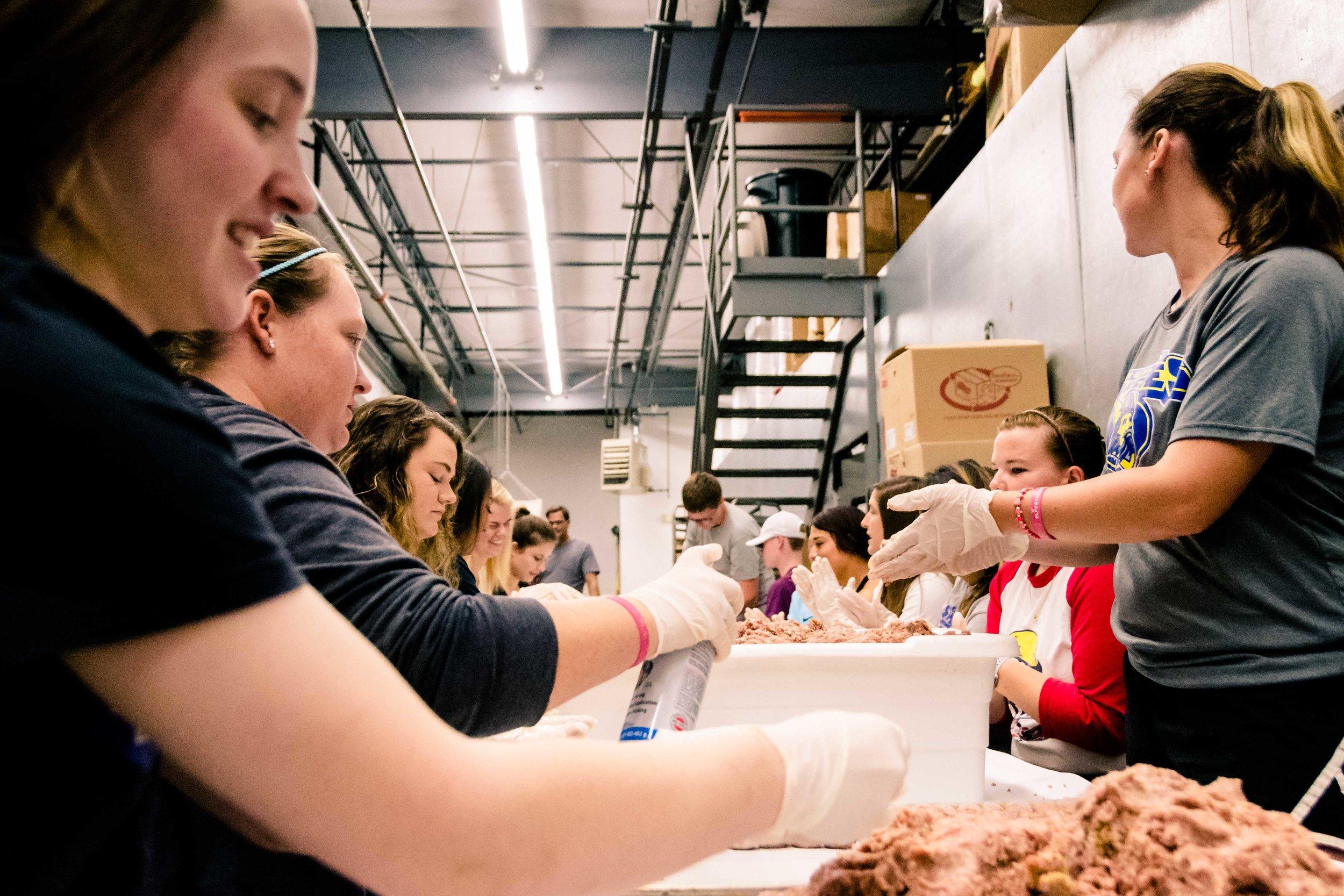 Bethany student Brittney Roush (left)of Visalia, Calif.,prepares meatballs with friends.