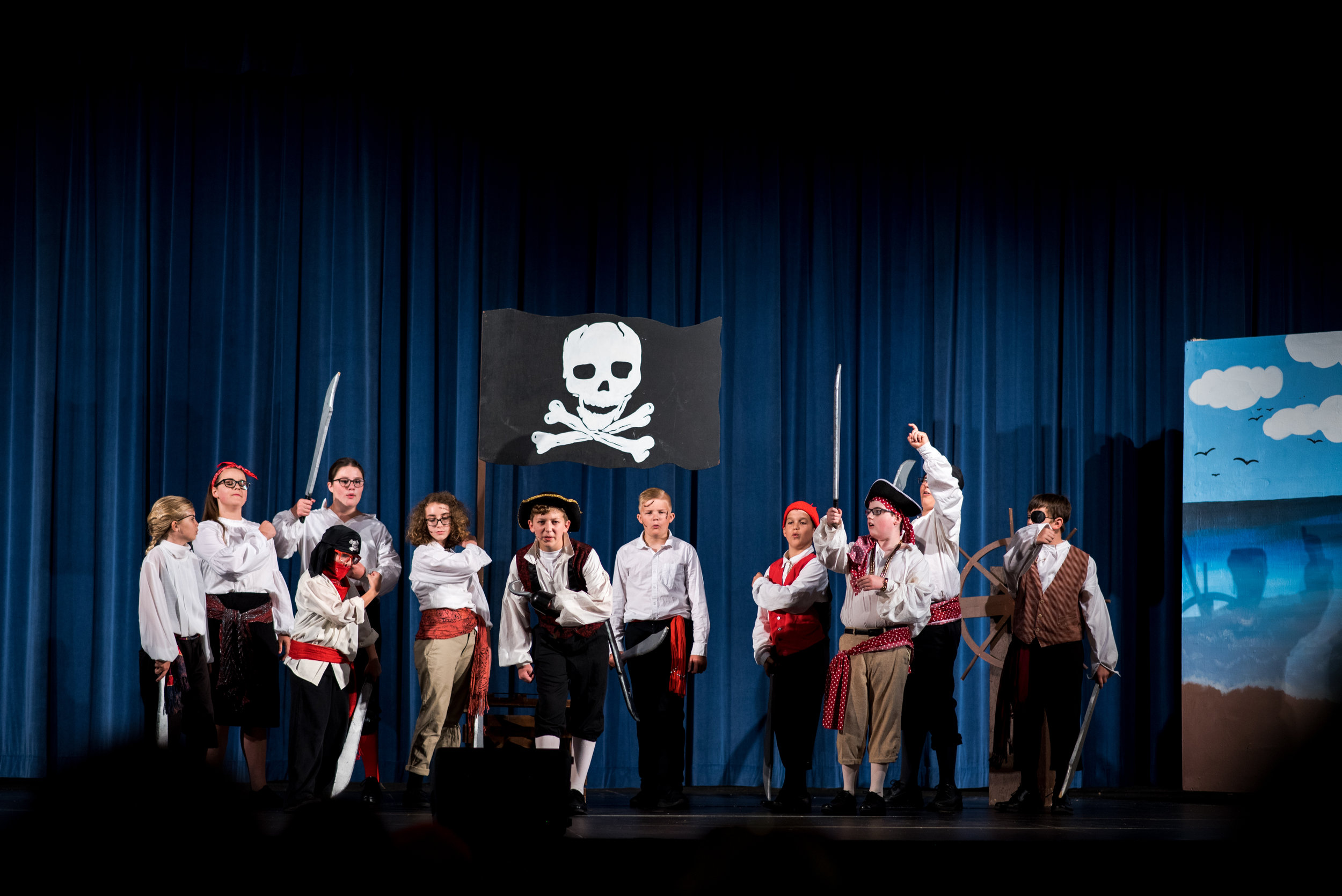A jolly band of singing pirates led by Captain Hook (sixth from left) played by Cael Kibler.