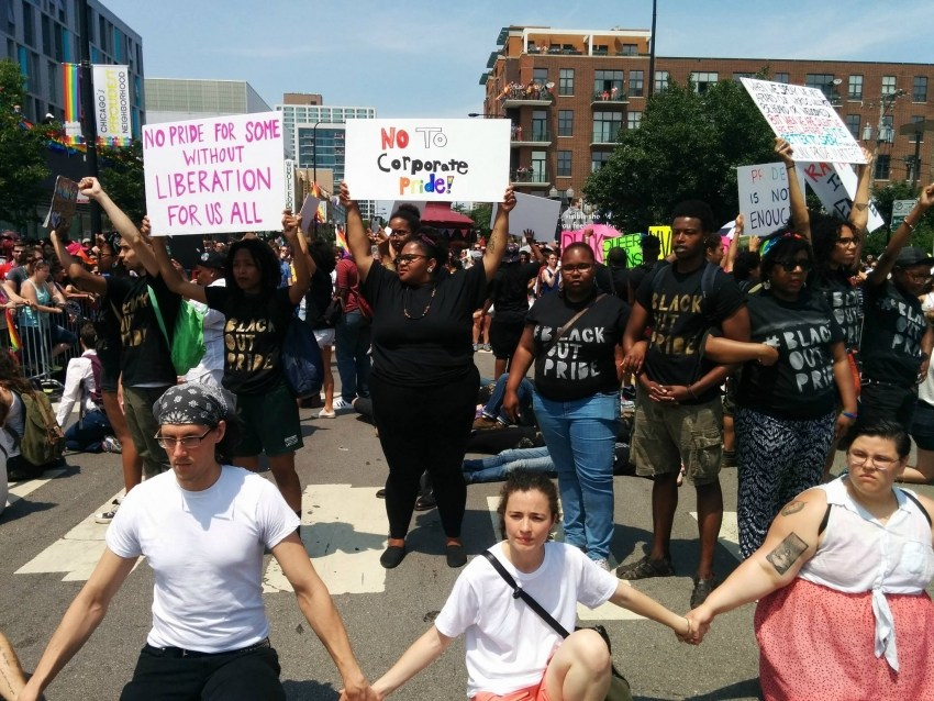 """Image: Activists and Organizers in the fore-ground are on their knees and holding hands. In the background, organizers and activists stand in front of a crowd and hold up posters that say: """"No Pride For Some Without Liberation For Us All""""; """"No to Corporate Pride"""" while wearing black t-shirts with """"Black Out Pride"""" inscribed on the front. To the right, three Black organizers are linked together at the elbows. Image is of the 2015 BlackOut Pride Demonstration in Lakeview during Pride Week in Chicago. Photo by Kelly Hayes."""
