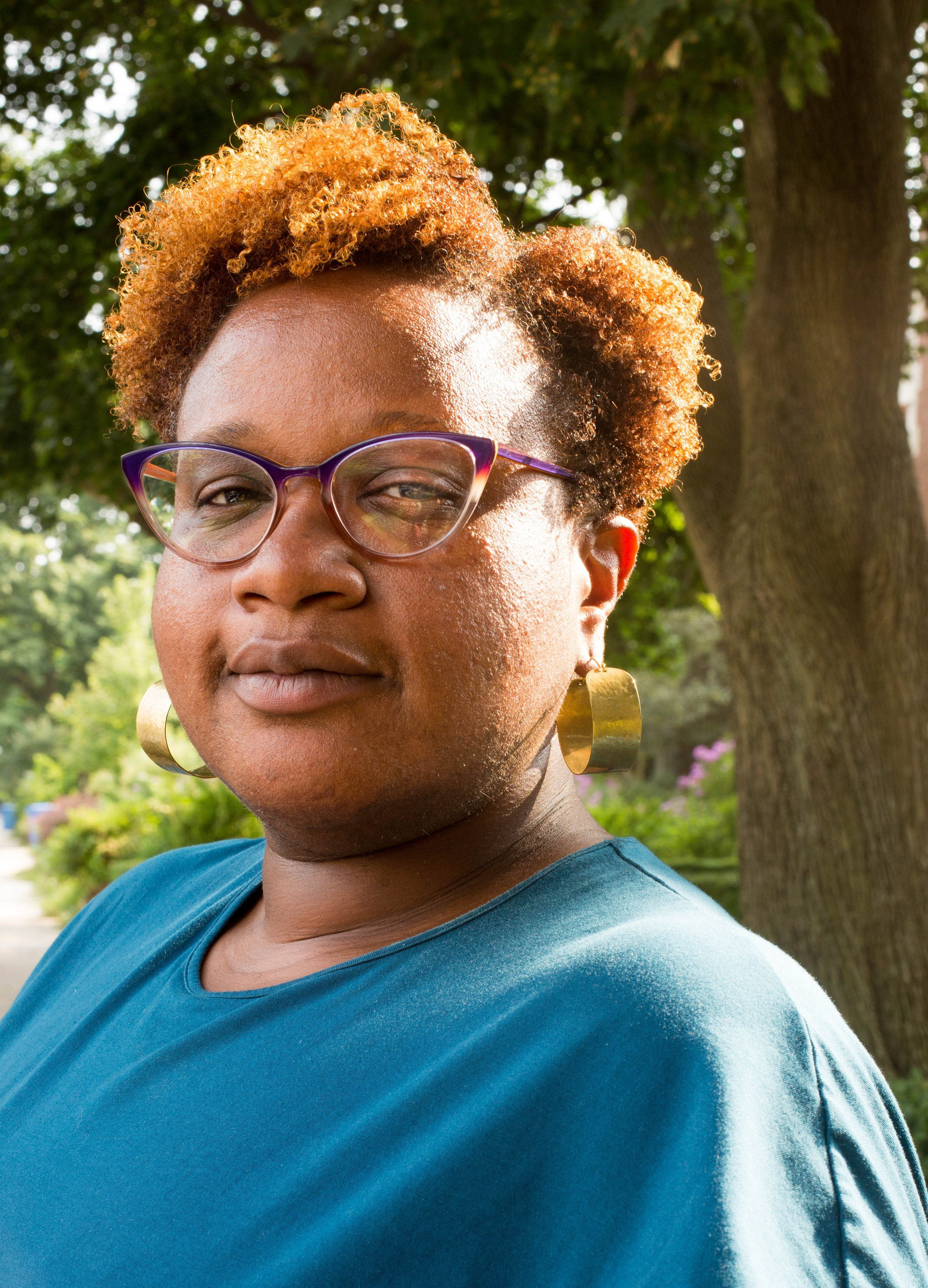 Image: Portrait of Erin Glasco. She is wearing a teal dress, copper earrings, and purple glasses, and looks directly at the camera with a slight smile while standing in front of trees and bushes of flowers. Photo by Ireashia Bennett.