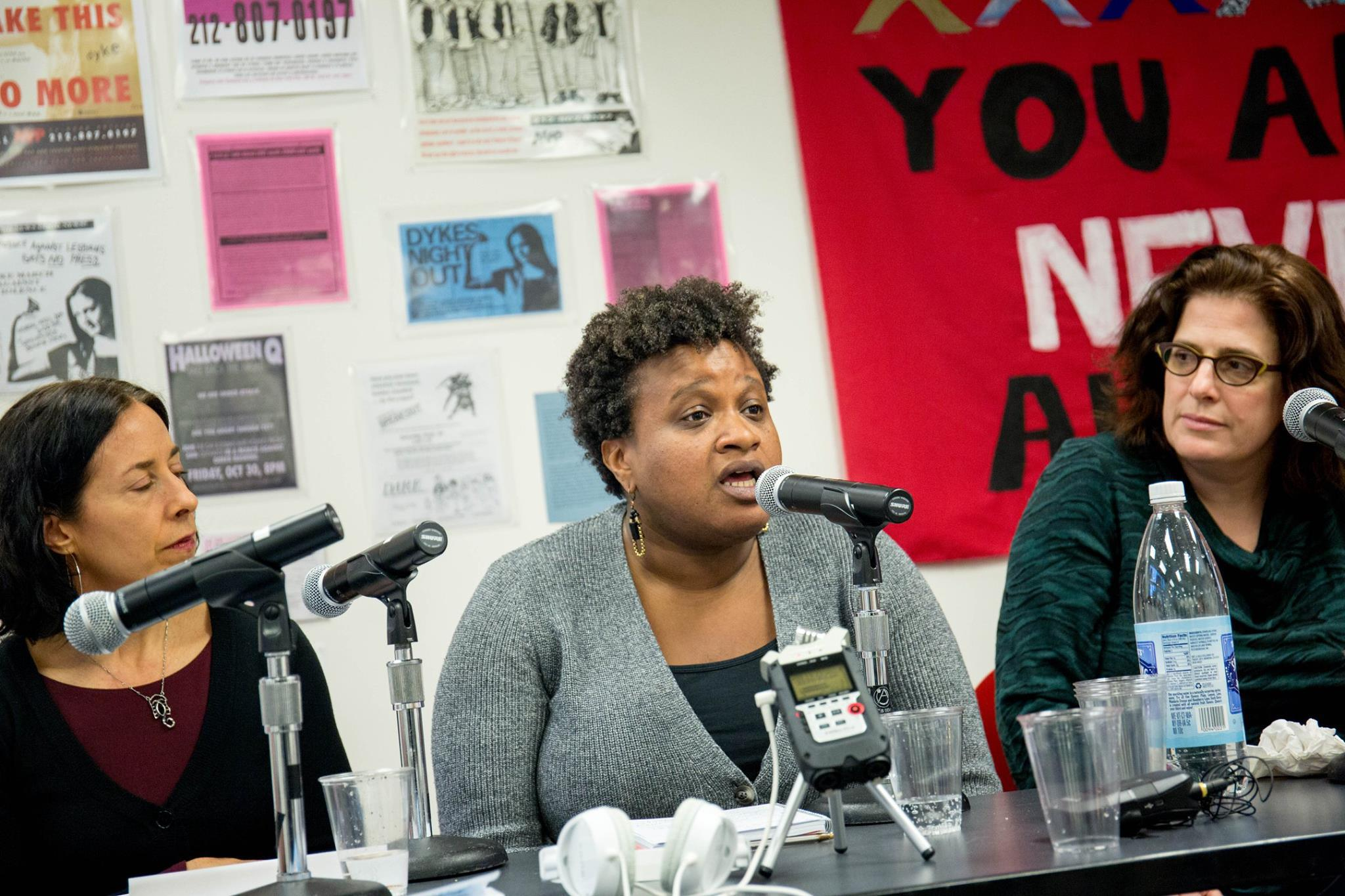 Image: Melissa Forbis (left), Erin Glasco (center) and Jennifer Brier (right) speak on the panel at the opening reception of Take Back the Fight: Resisting Sexual Violence from the Ground Up at Pop-Up JUST Art Gallery April 2018. Erin Glasco, wearing a black shirt and gray sweater, speaks as Melissa Forbis and Jennifer Brier listen and watch beside her. Photo by Ireashia Bennett.