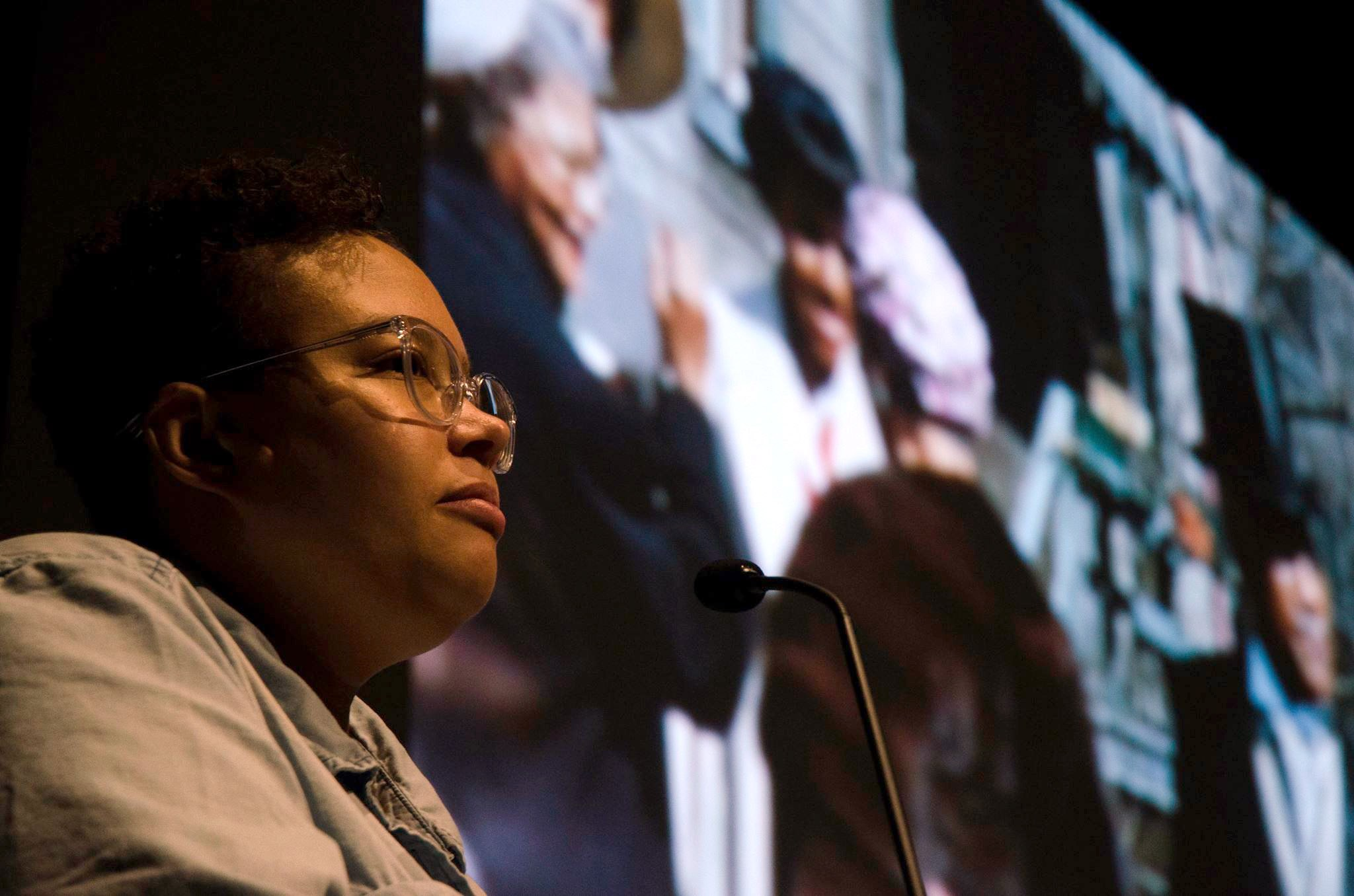 Image: Close-up shot of Candace Ming, who wears a light denim shirt and clear-framed glasses. Candace looks beyond the camera as she shares film selections from the SSHMP archive at the Logan Center Five Year Bash on October 7, 2017. Photo by Martin Awano, Film still from the Jean Patton Collection, courtesy of the South Side Home Movie Project.