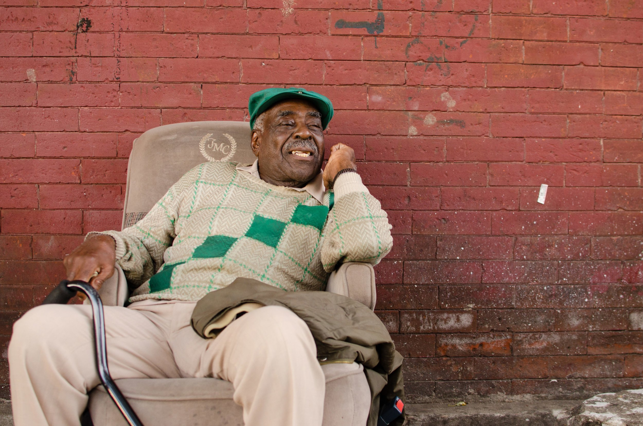 Image: An older Black man reclines in a tan suede chair with his left elbow resting on the chair's armrest. His metal cane rests on his right leg. Behind him is a red brick wall with markings and imperfections on it. He gazes to the right of the camera with a open-mouthed smile on his face. He is wearing beige slacks, a beige shirt and a green, white, and a beige sweater with a green hat. Photo courtesy of the artist.