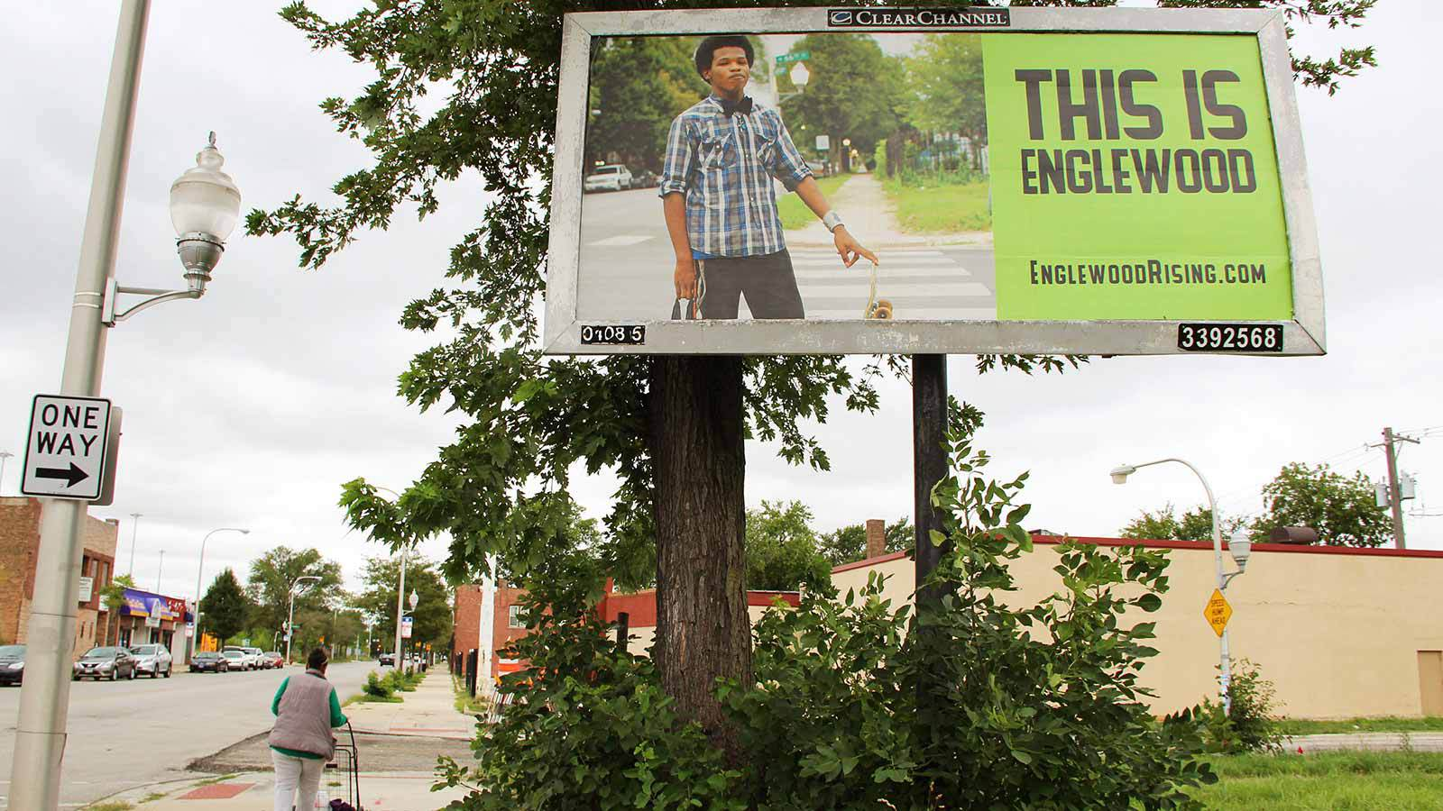 """Image: To the top right, a Englewood Rising billboard sits above a green bush. The billboard features a young Black man with a medium-sized afro, smiling. He is wearing a plaid shirt and a black bow-tie. In his left hand, he rests his index finger on his skateboard. He is holding a plastic bag in his right hand. Beside his image in black text against lime green background reads: """"This is Englewood."""" On the lower left, a person with a grocery cart walks underneath the billboard. Photo courtesy of the artist."""