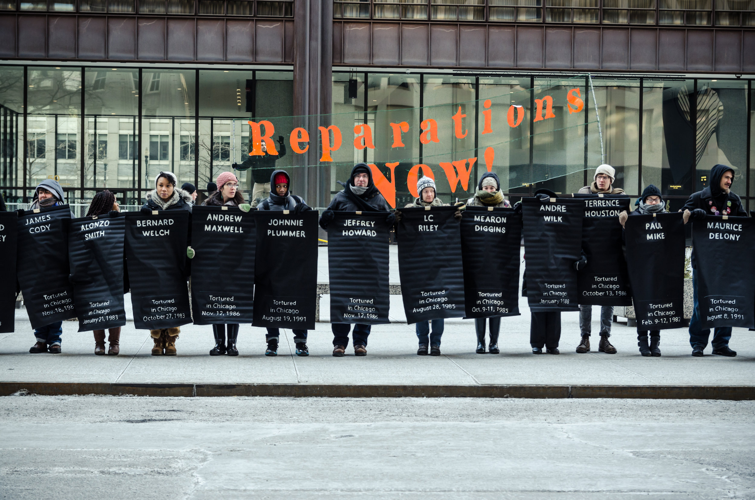 """Image: People lined up facing the camera, holding up black posters with the names of victims of torture by Chicago police inscribed in white. Behind them is a transparent banner with the words """"Reparations NOW!"""" inscribed in orange.  The photo  was taken February 2015 at the Rally for Reparations organized by The Chicago Torture Justice Memorials, Project NIA, Amnesty International USA, and We Charge Genocide. Photo courtesy of the artist ."""