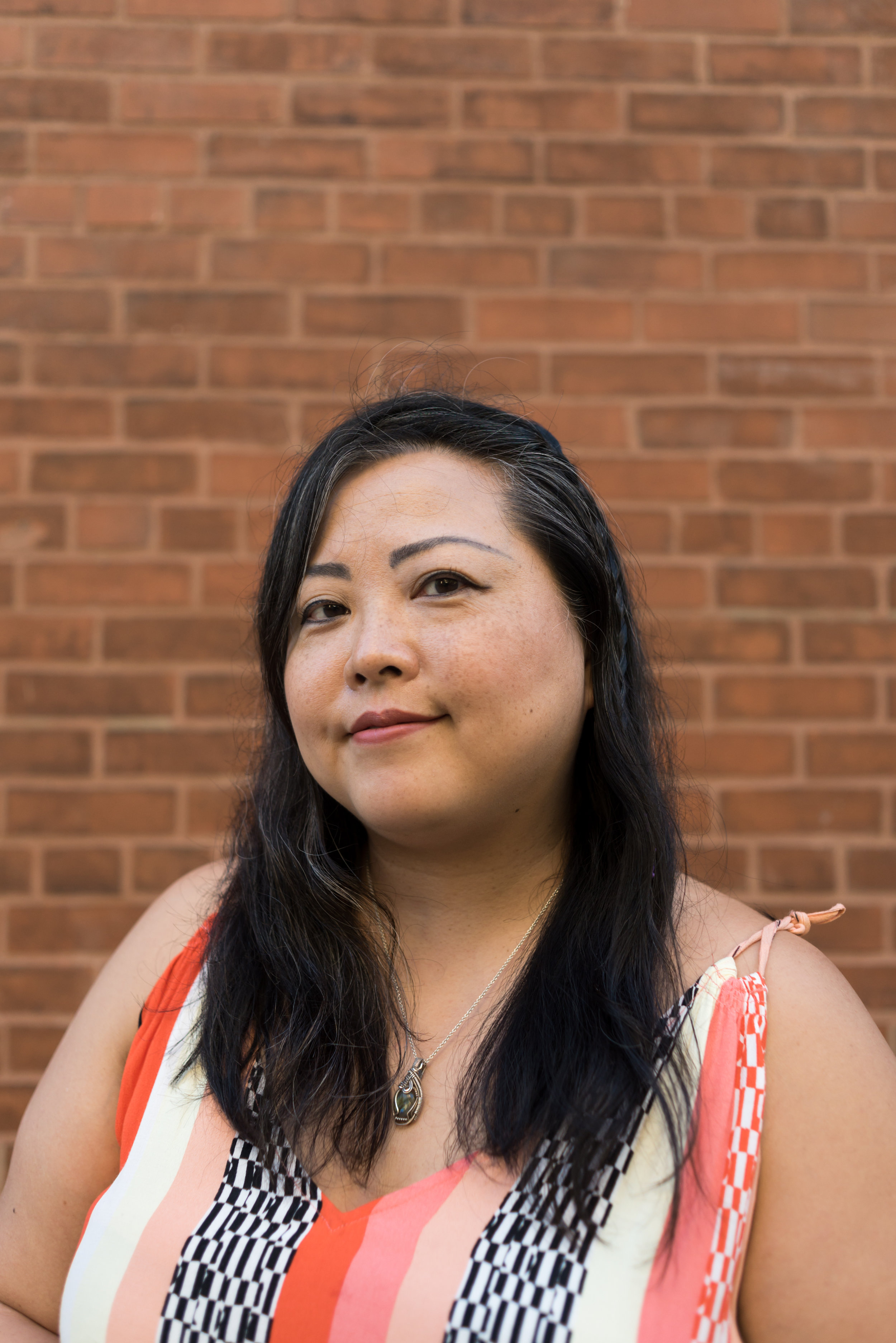 Image: A portrait of the artist Sarah-Ji standing in front of a brick wall wearing a patterned dress. She looks directly at the camera with a slight smile. Portrait captured by Ireashia Bennett.