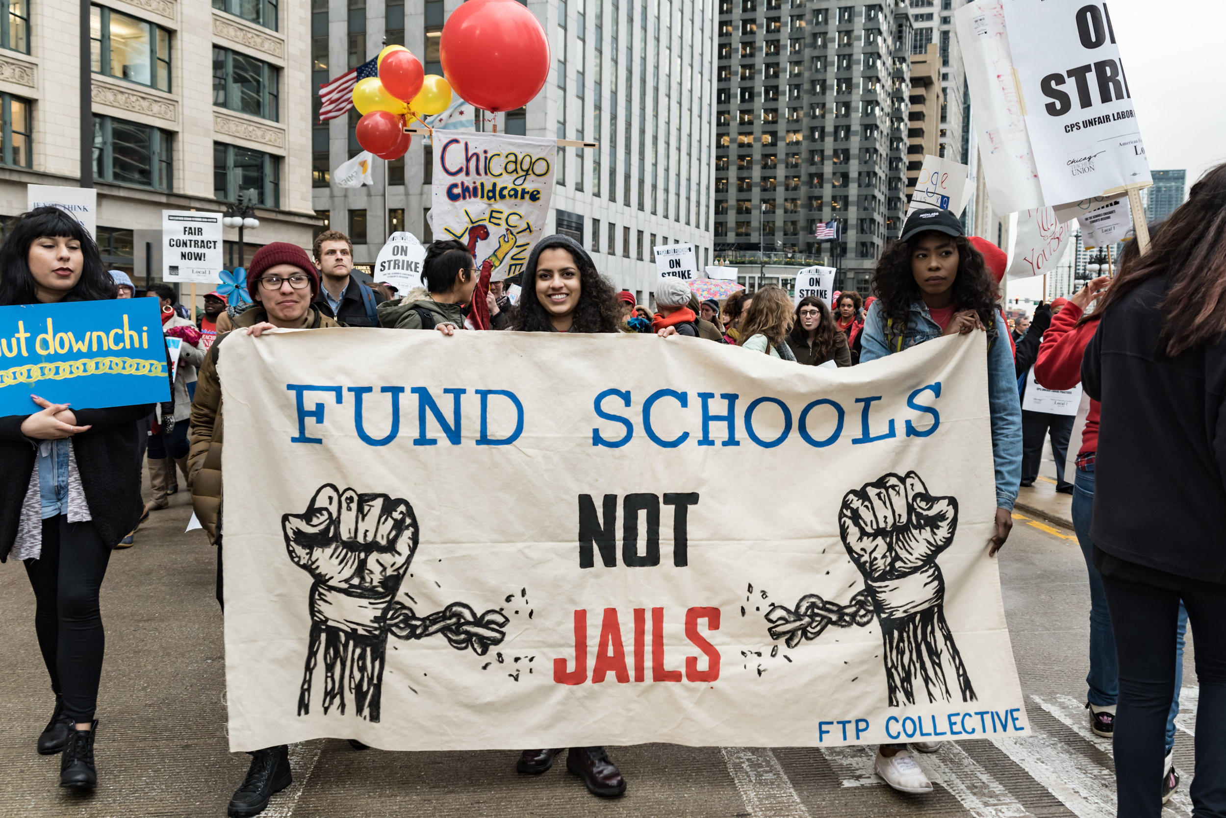 """Image: Photo of a group of people rallying in downtown Chicago. In the center of the image are three people of color holding up a sign which says: """"Fund Schools Not Jails"""" in the center. On either side of the words are images of painted fists with broken shackles around the wrists. On the bottom right of the poster is """"FTP Collective."""" Photo was taken April 2016 at the Shut Down the Chi Rally. Photo courtesy of the artist."""