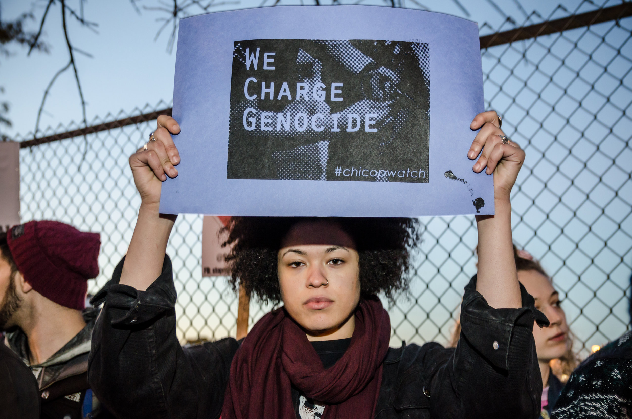 """Image: A young person of color stands in front of a chain-link fence, looking directly at the camera. They are holding up a poster with an image that has the words """"We Charge Genocide"""" superimposed in the center of the poster. The hashtag #chicopwatch is placed on the lower right corner of the poster. Photo taken October 22, 2014, at the Break Down the Wall of Silence Protest Against Police Brutality, organized by We Charge Genocide. Photo courtesy of the artist."""