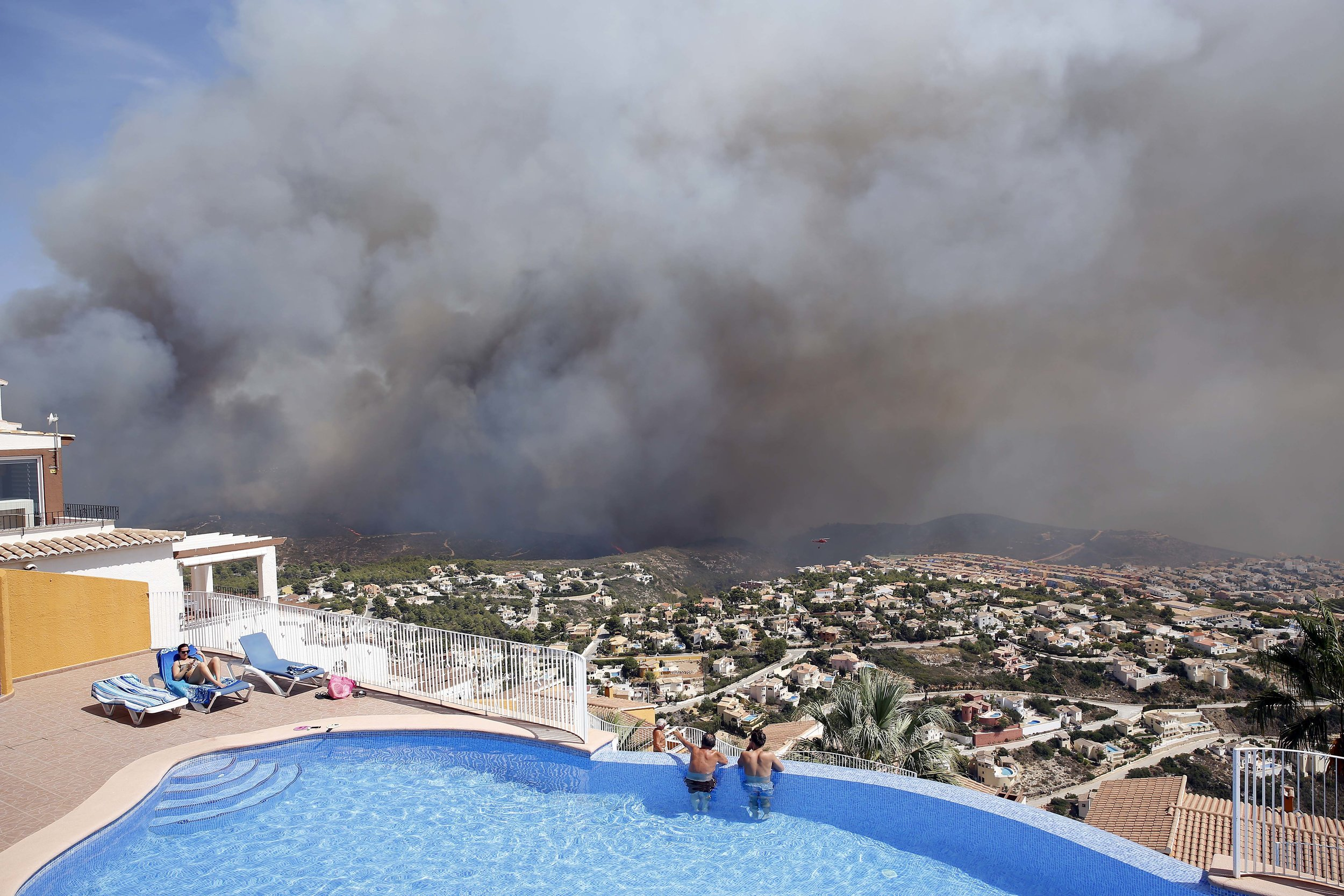 Two men look out from a swimming pool at a wildfire as it burns nearby in eastern Spain. Scientists say southern Spain will become desert and deciduous forests will vanish from much of the Mediterranean basin unless global warming is reined in sharply. They concluded that any warming above 2 degrees Celsius would cause changes not seen in 10,000 years. (AP Photo/Alberto Saiz, file)