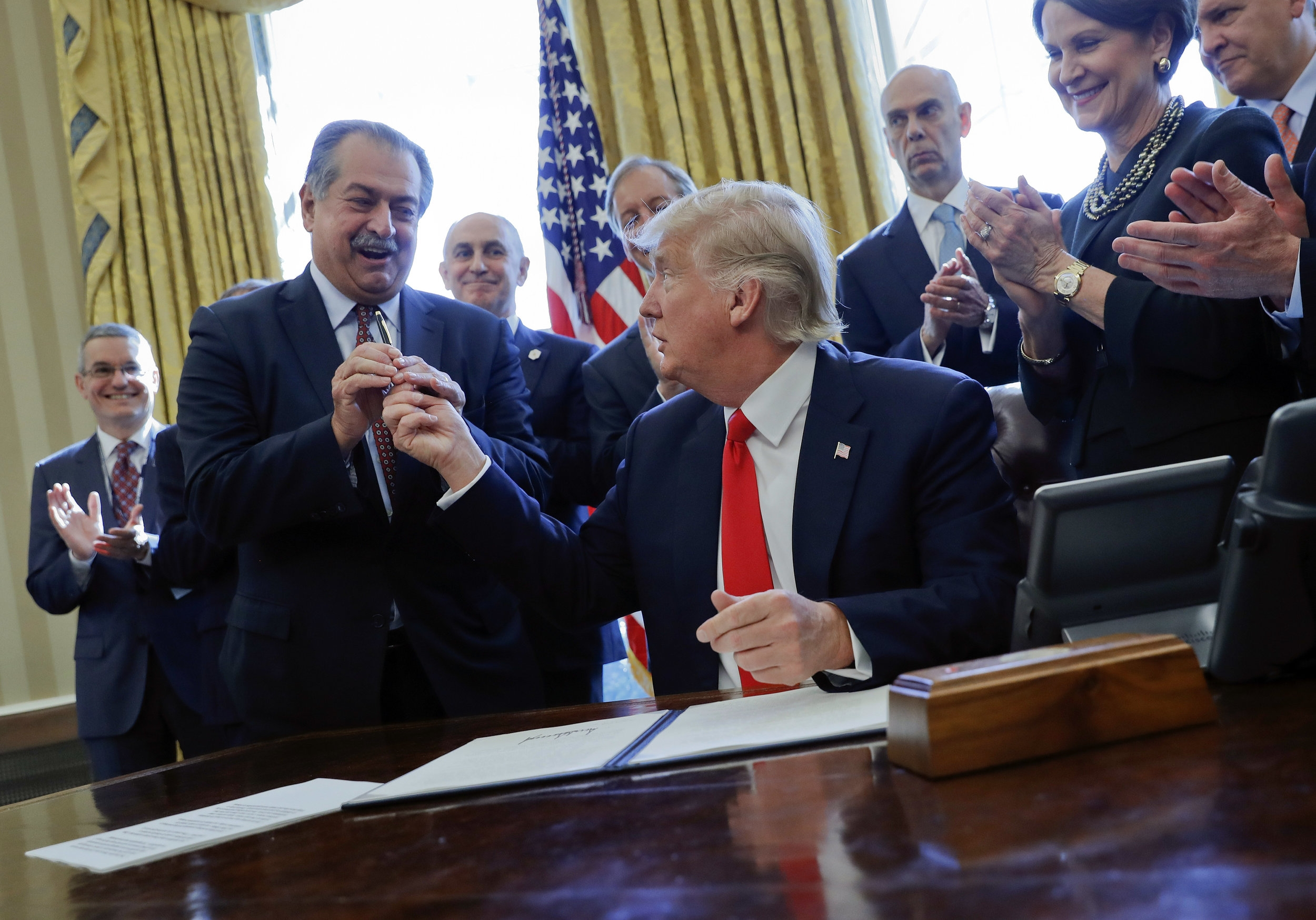 In this Feb. 24, 2017 photo, President Donald Trump gives the pen he used to sign an executive order to Dow Chemical President, Chairman and CEO Andrew Liveris, as other business leaders applaud in the Oval Office. Environmental Protection Agency Administrator Scott Pruitt's schedule shows he met with Liveris for about a half hour on March 9 during a conference held in Houston. Twenty days later Pruitt announced his decision to deny a petition to ban Dow's chlorpyrifos pesticide from being sprayed on food, despite a review by his agency's own scientists that concluded ingesting even minuscule amounts of the chemical can interfere with the brain development of fetuses and infants. (AP Photo/Pablo Martinez Monsivais, File)