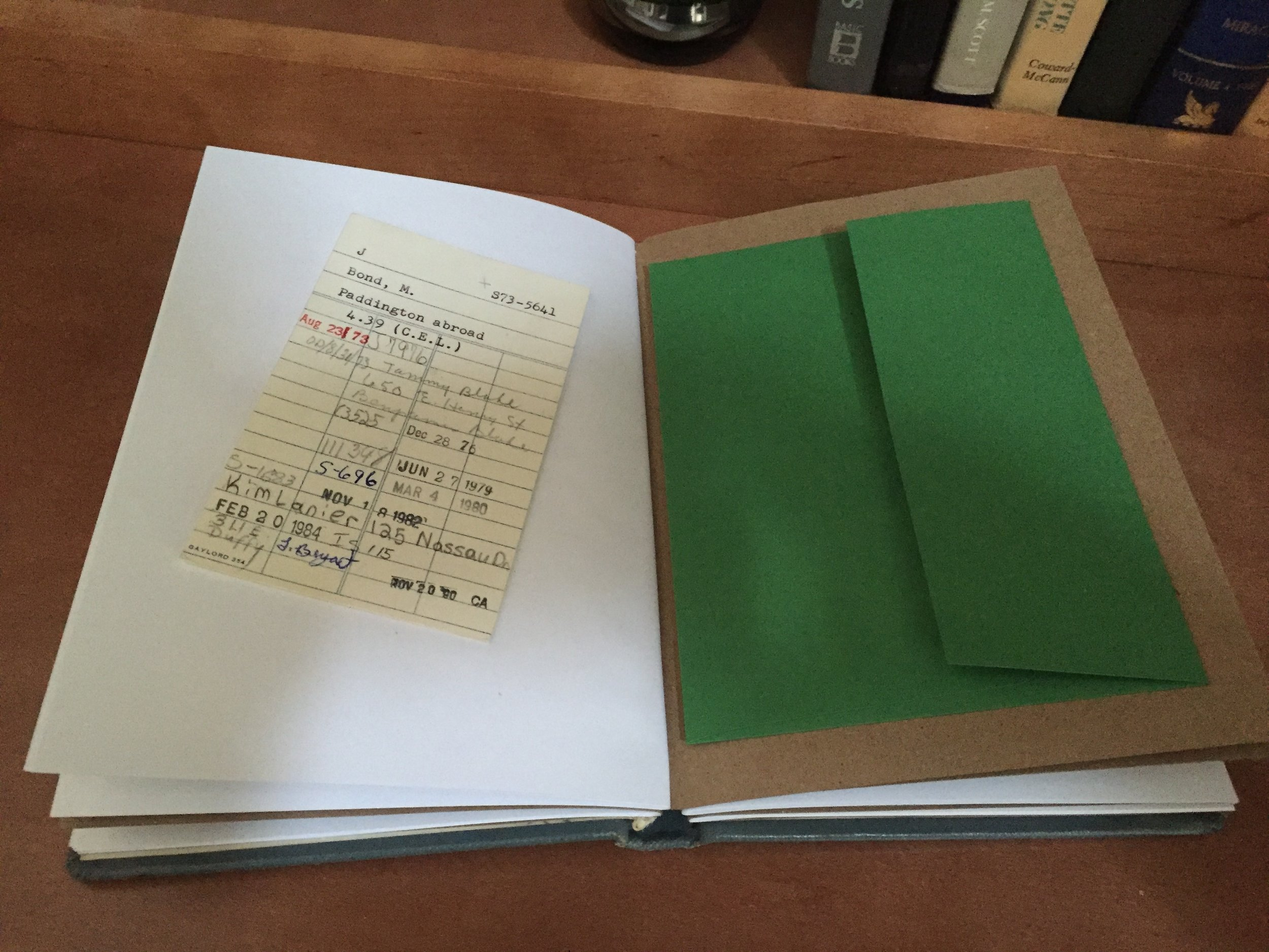 """Paddington Abroad comes with the original Library's """"Date Due"""" card. Premium stock blank white paper secured to 65-lb. Kraft paper make up the signature pages. Premium stock green envelopes are used at the end of the signature blocks for storage."""