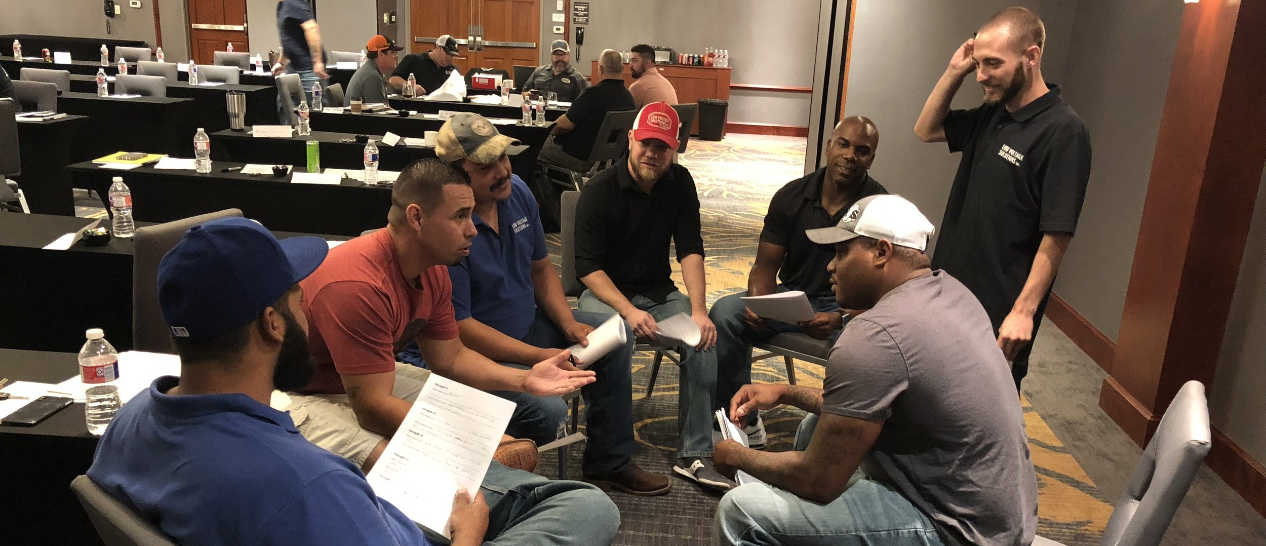 Low Voltage Solutions employees discuss their leadership training in a conference room.