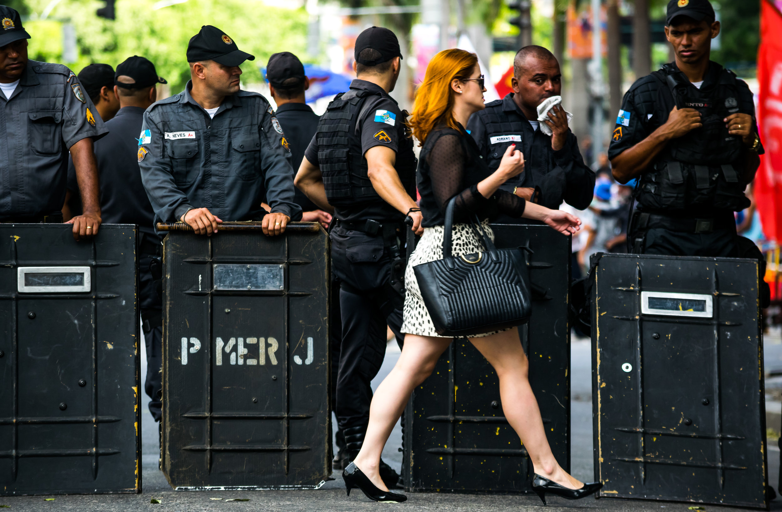 A woman walks past a police line in downtown Rio De Janeiro. For many the protests have become such a regular occurrence that they are no more than an inconvenience or part of the background.