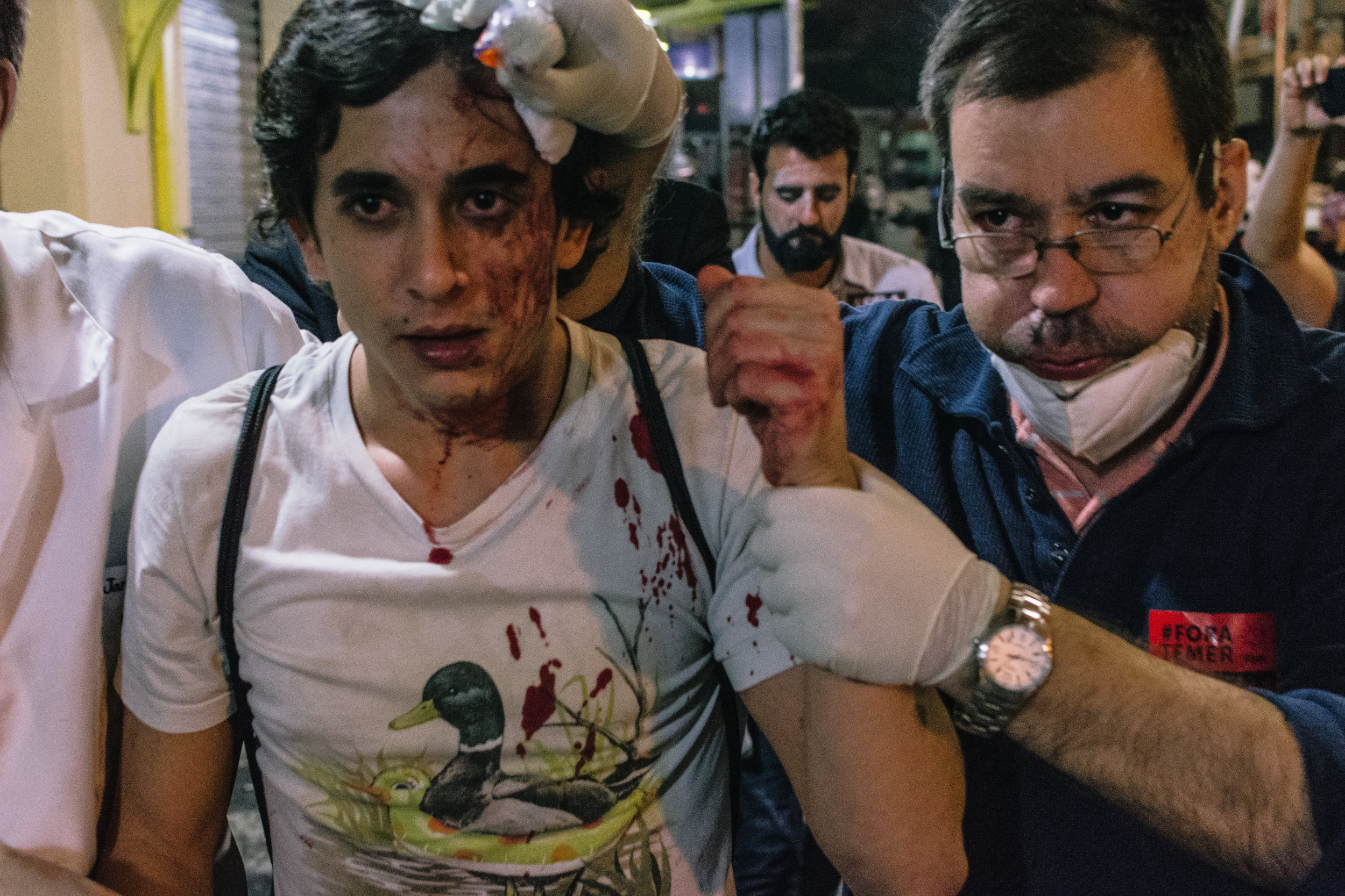 Volunteer medics lead a man injured during protests to an ad-hoc casualty collection area.