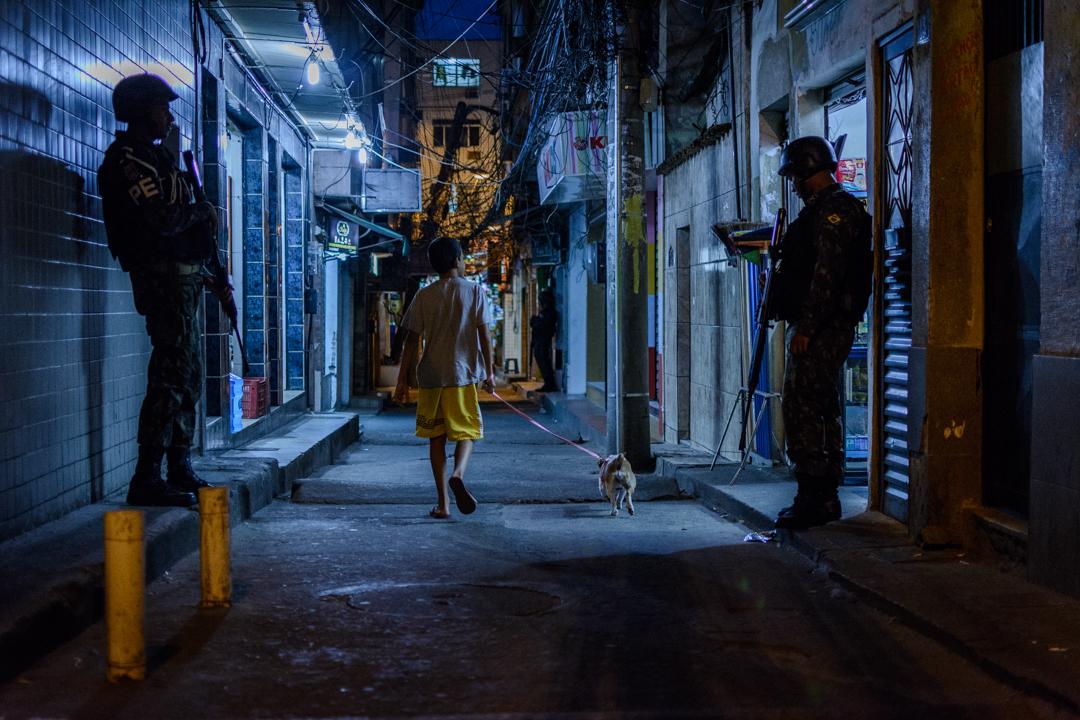 A Boy and His Dog Walk Between Soldiers in Rocinha Favela, Rio de Janeiro.